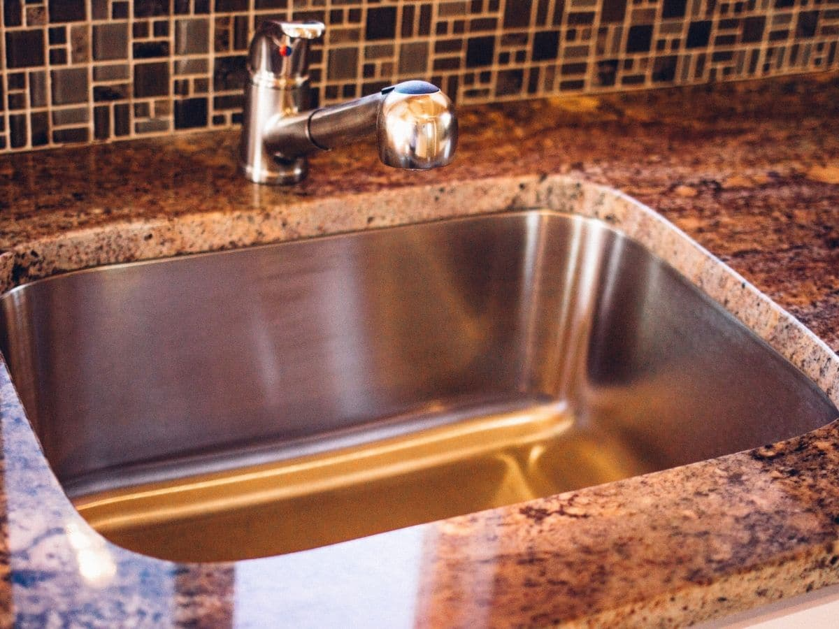 Stainless steel sink in counter in front of tile backsplash