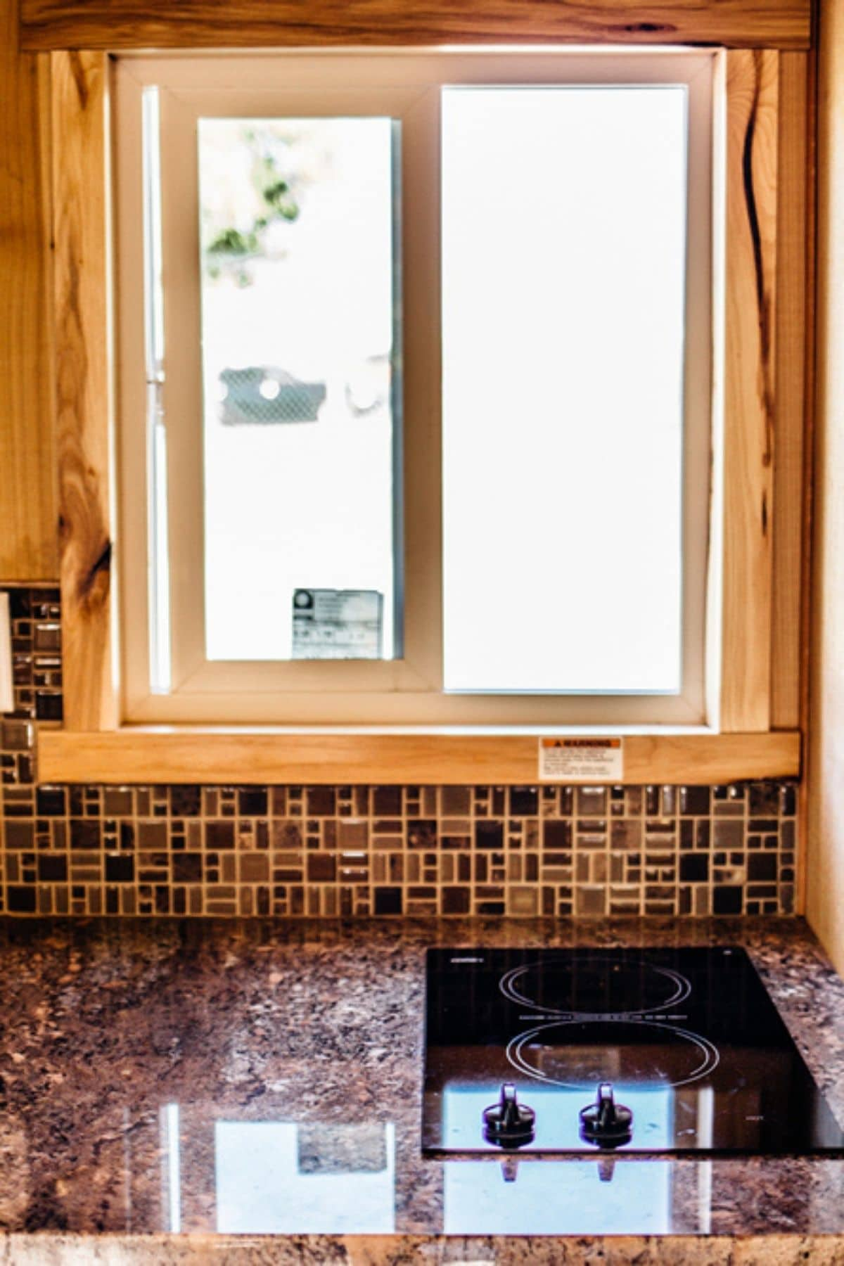 Colorful earth tone tile work underneath window above cooktop