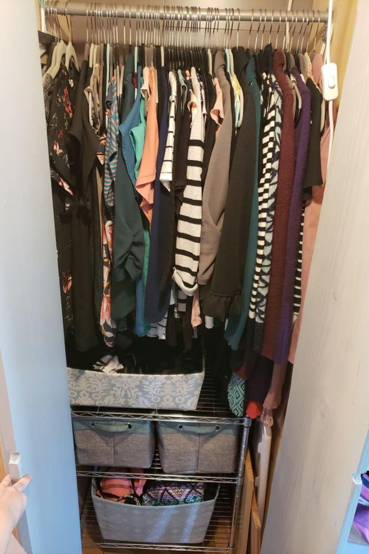 Closet with clothes hanging and baskets under on floor