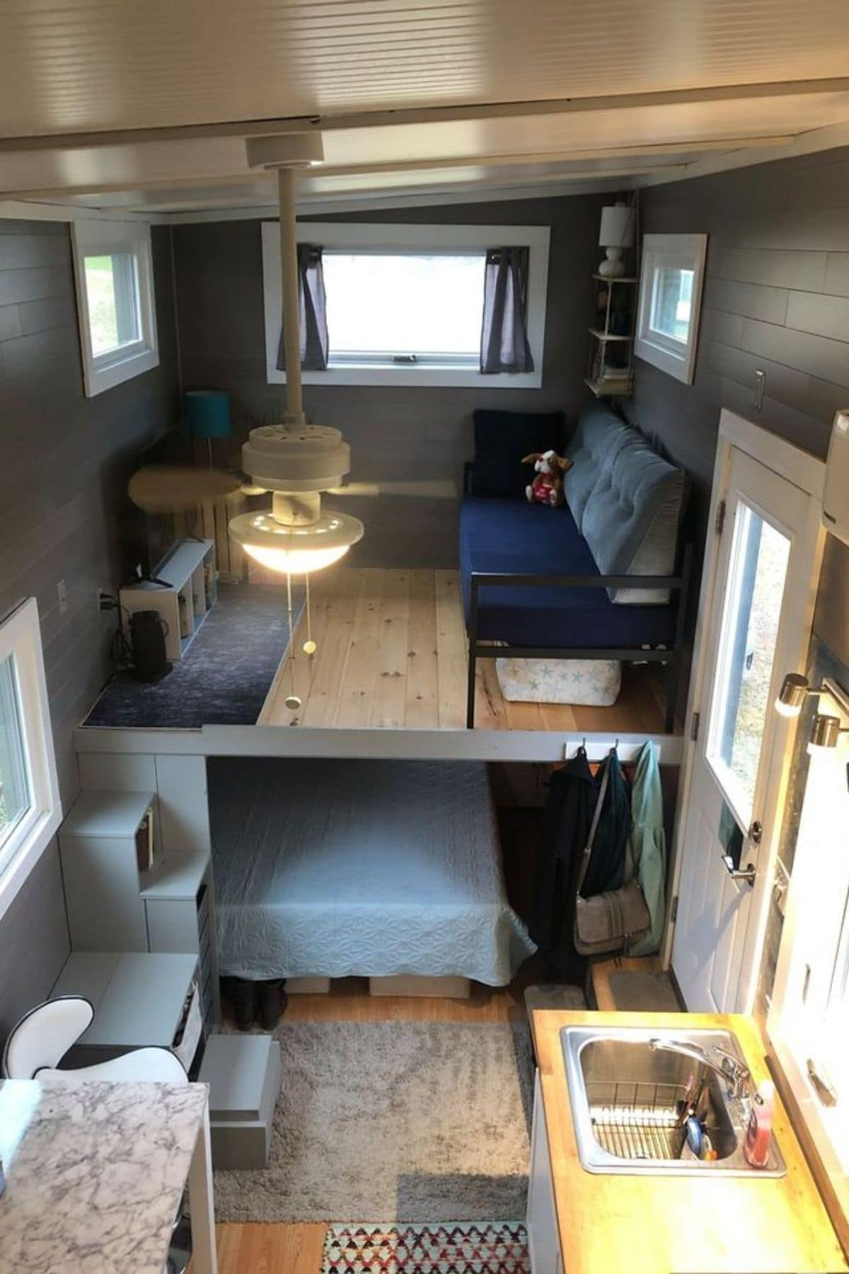 View of loft with sofa and bed underneath in cubby