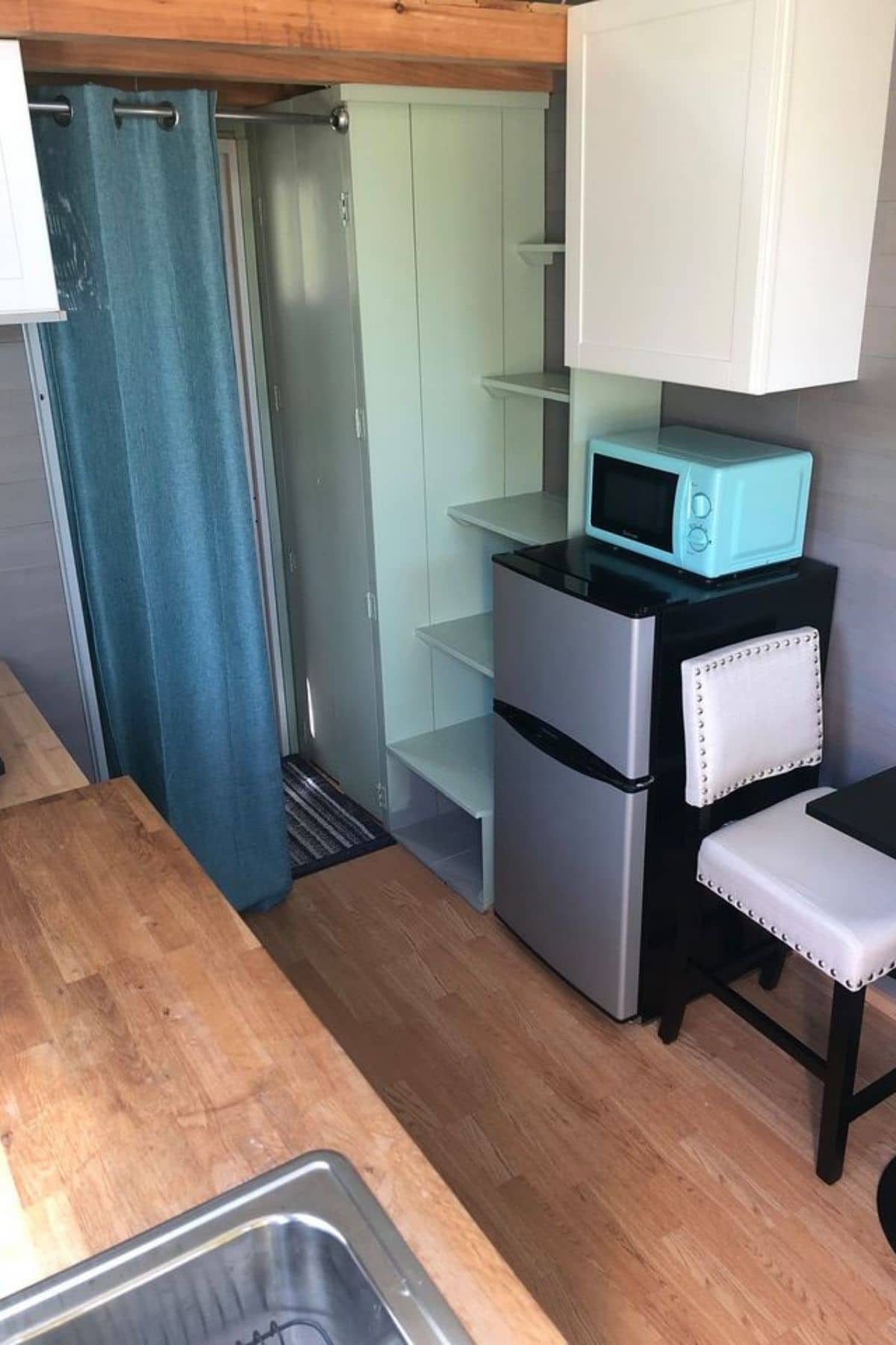 Mini refrigerator next to light green stairs and closet