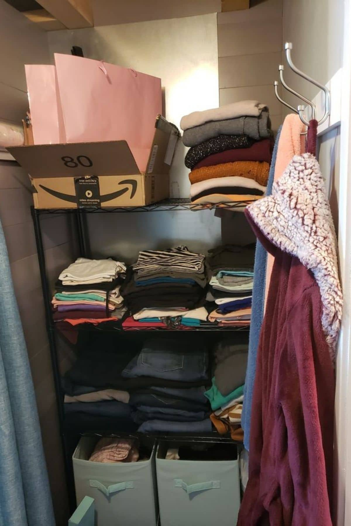 Storage shelf stacked with clothes next to hook holding robe