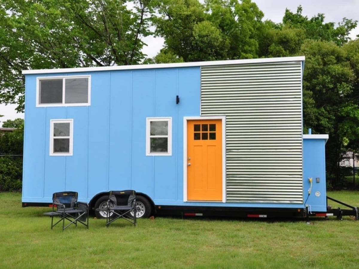 Light blue tiny house on wheels with orange door and white trim