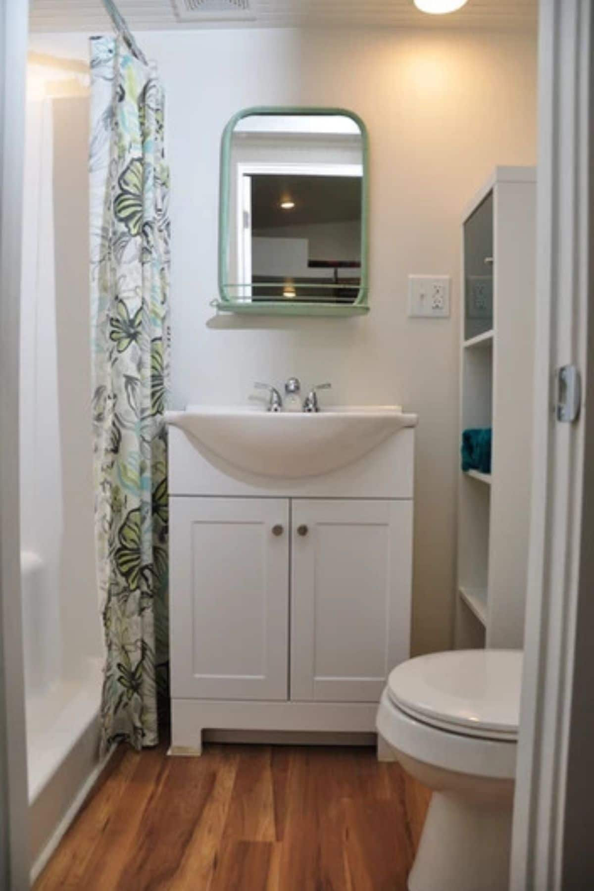 Modern white vanity under wall mounted mirror by shower curtain
