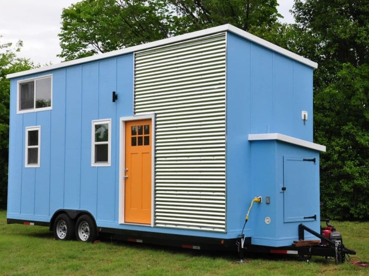 Front of blue tiny house with orange door