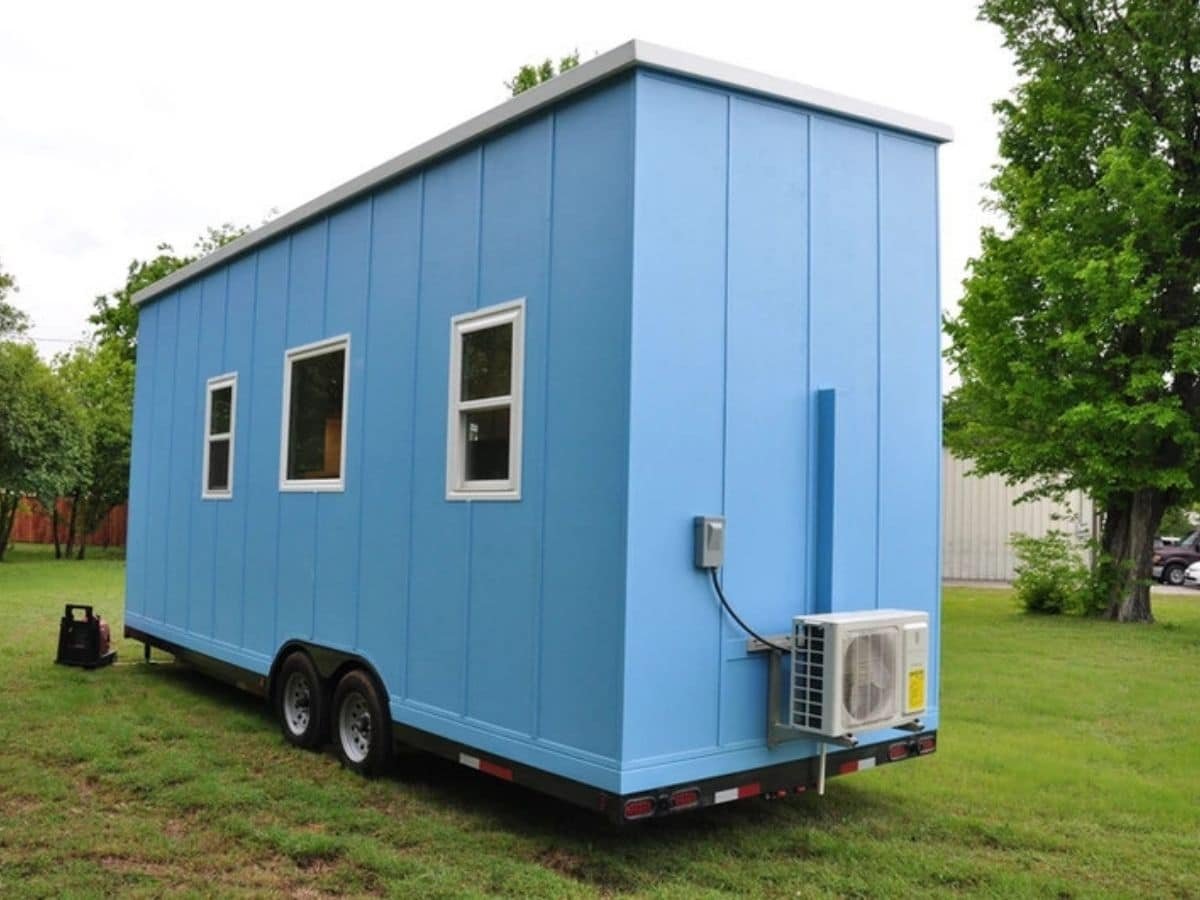 Back side of blue tiny house with three small windows