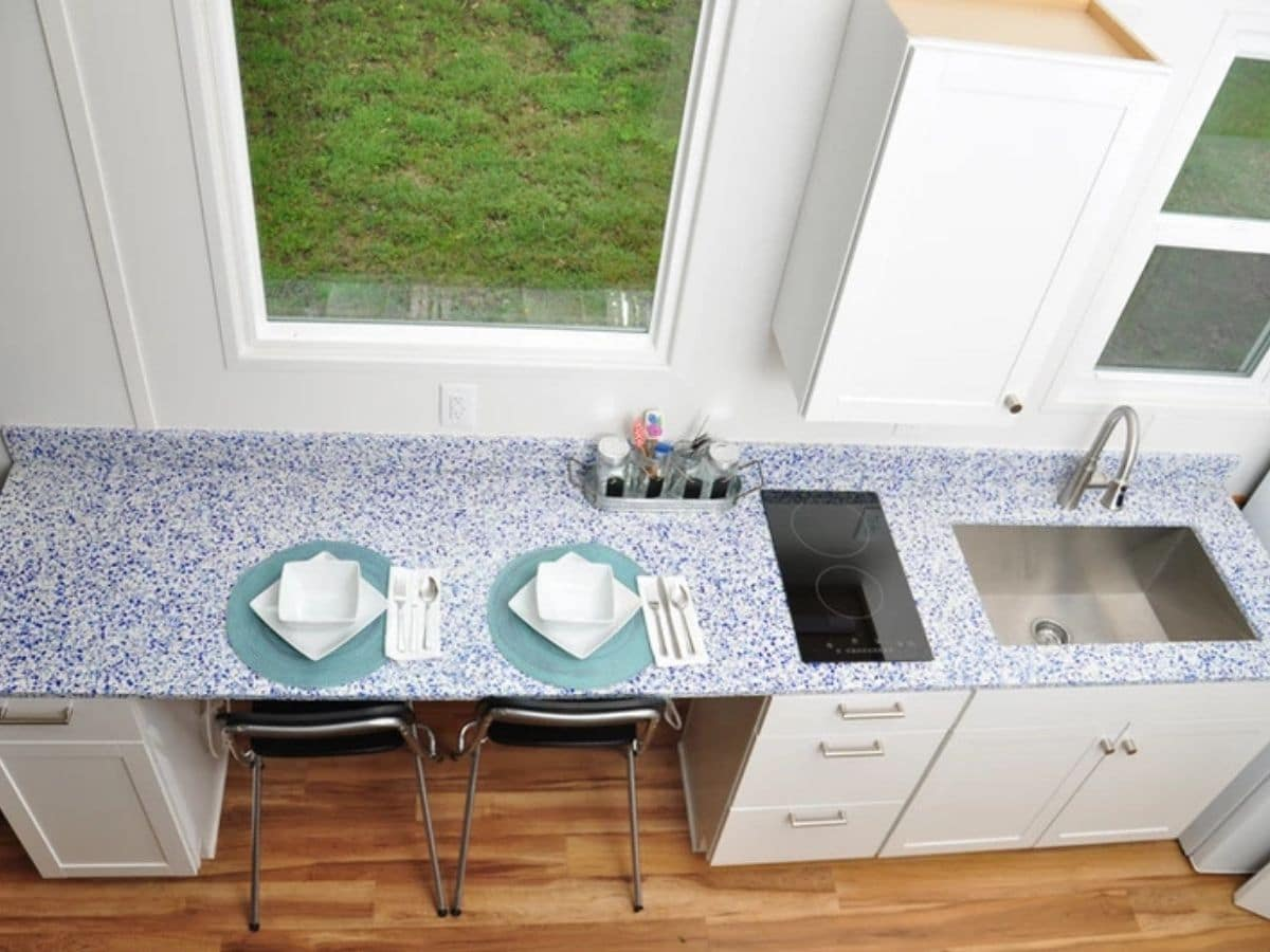 View from above kitchen counter showing cooktop sink and place settings