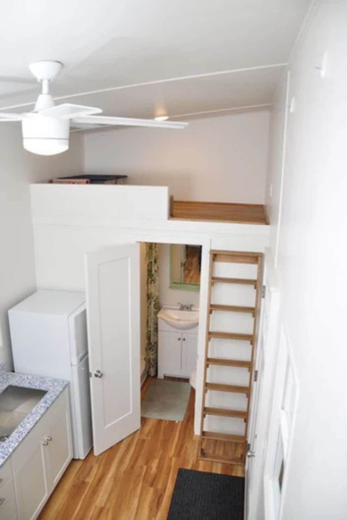 Small loft above bathroom with wood ladder