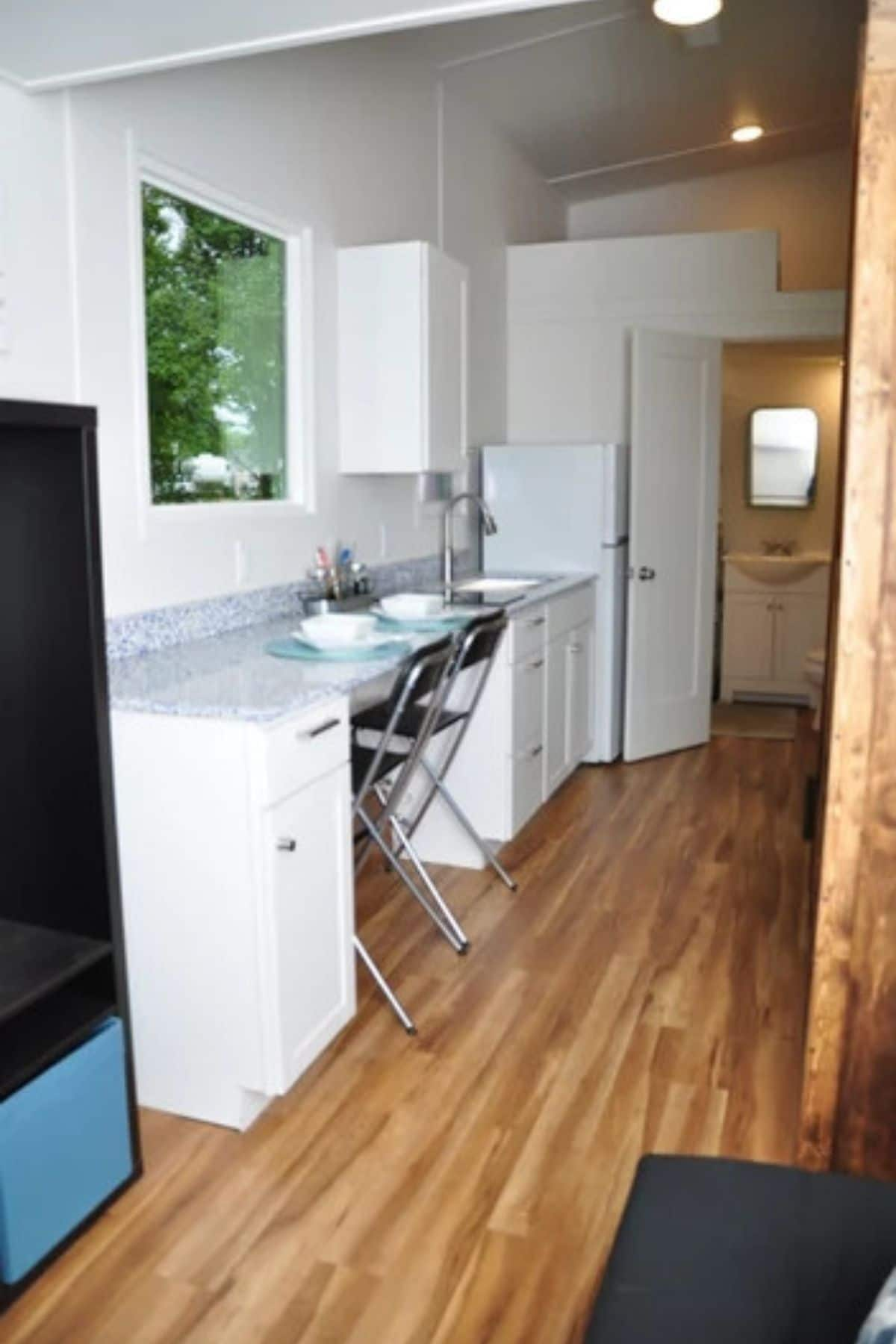 Looking into kitchen with chairs tucked under long counter