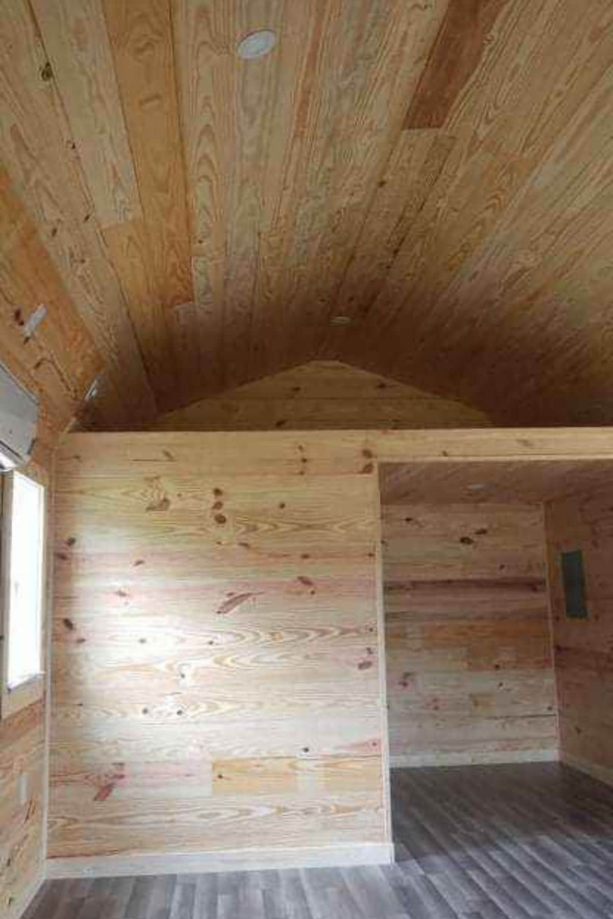 Open loft above tiny house bathroom with light wood walls