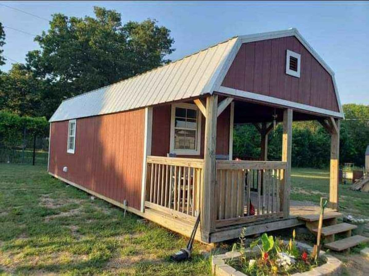 Red tiny house shed conversion on grass lawn