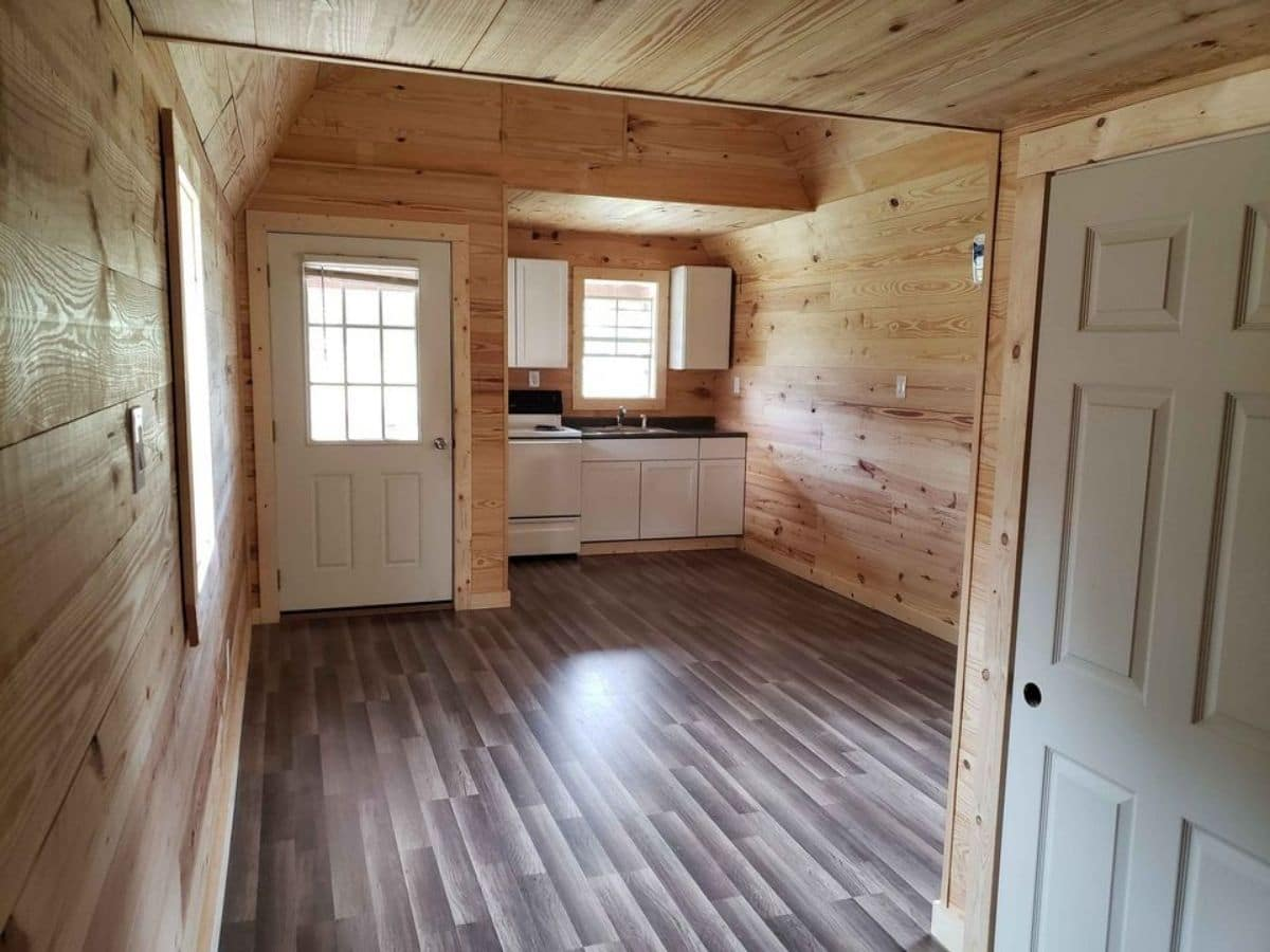 White front door and kitchenette surrounded by natural wood walls and floors