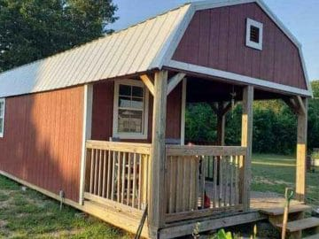 Red shed cabin with wood porch and loft