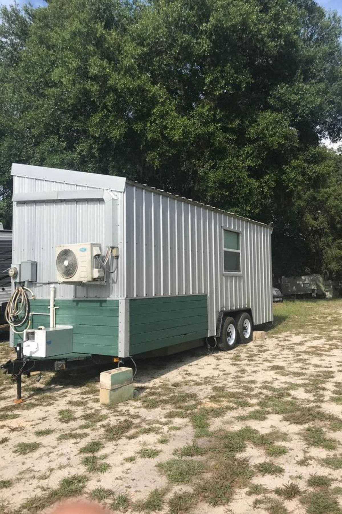 Back side of white and green tiny house on grassy lot