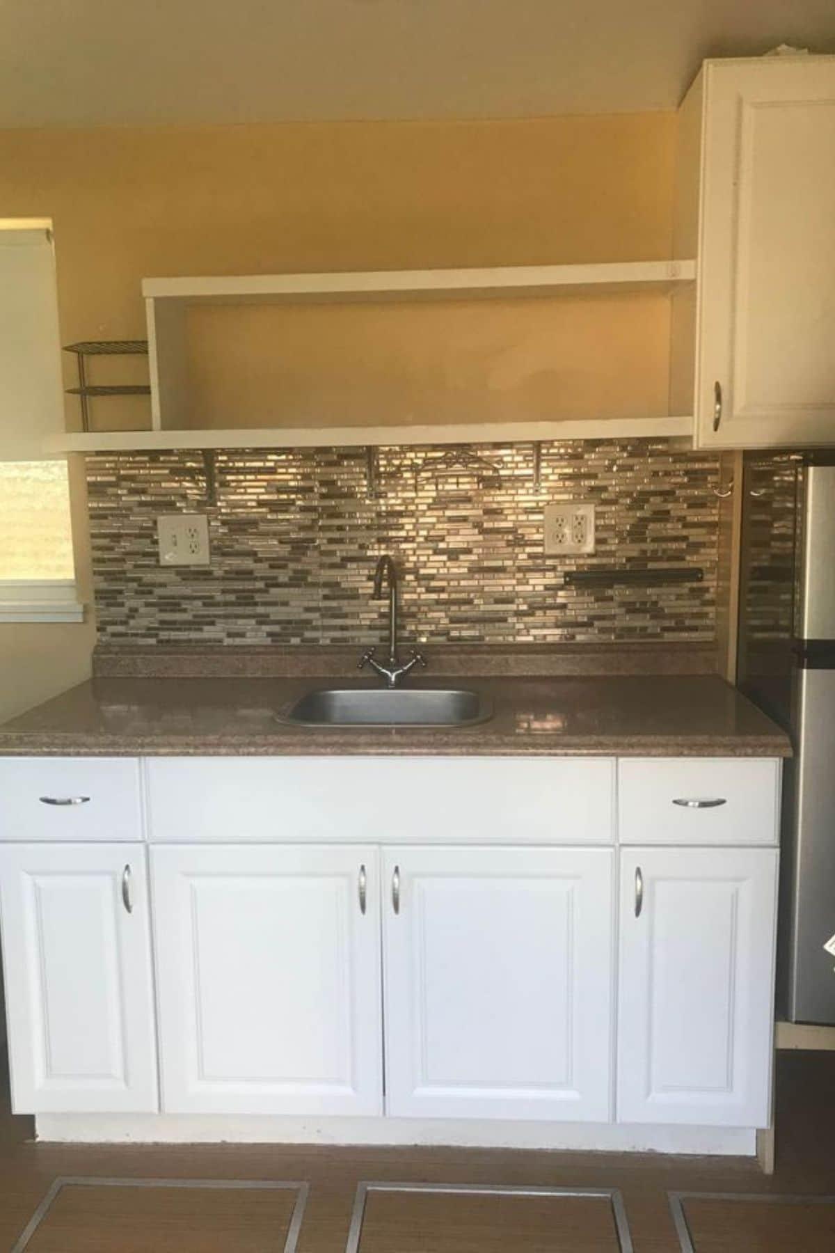 White kitchen cabinets under multi colored tile backsplash