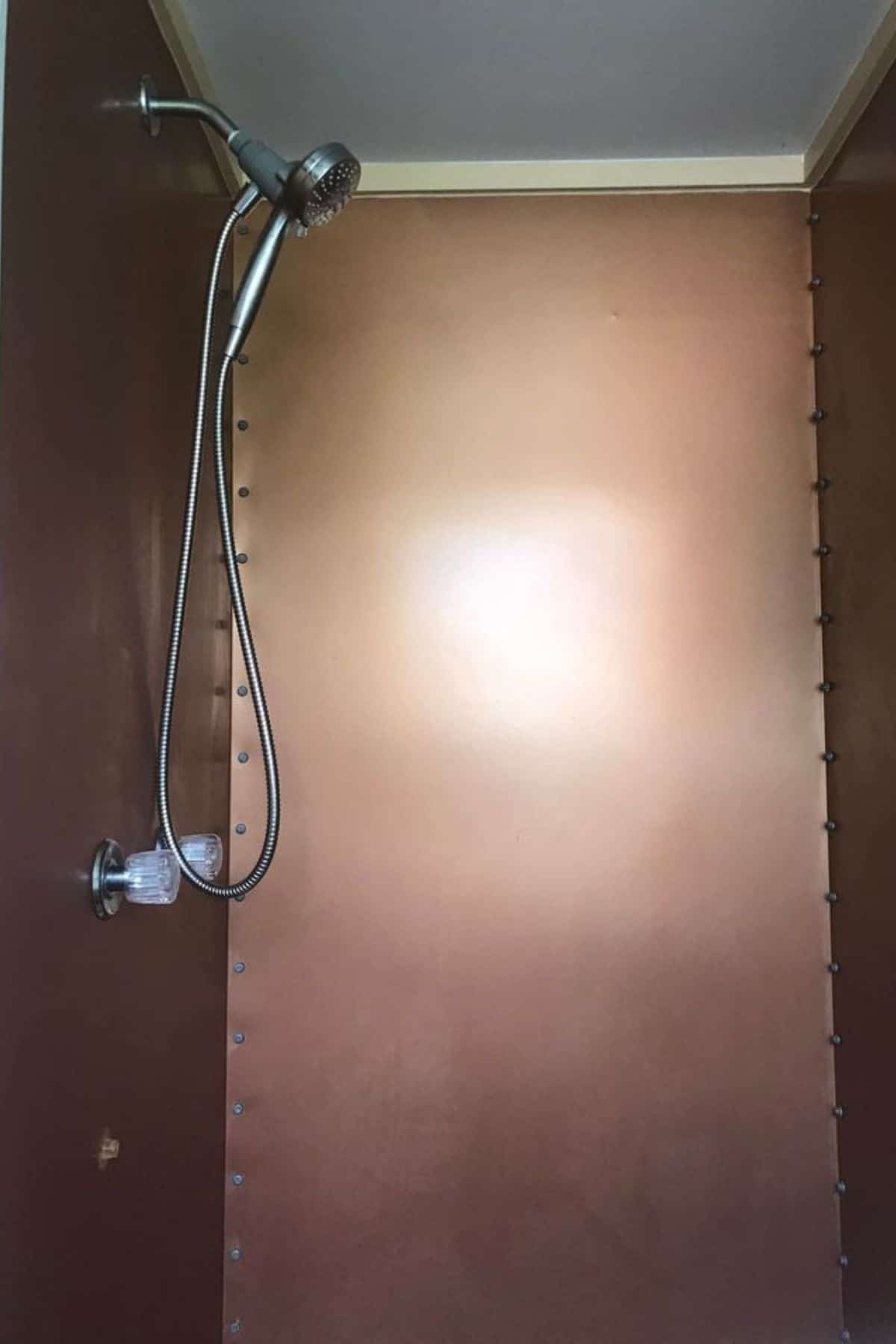 Copper wall in shower with detachable shower head on wall