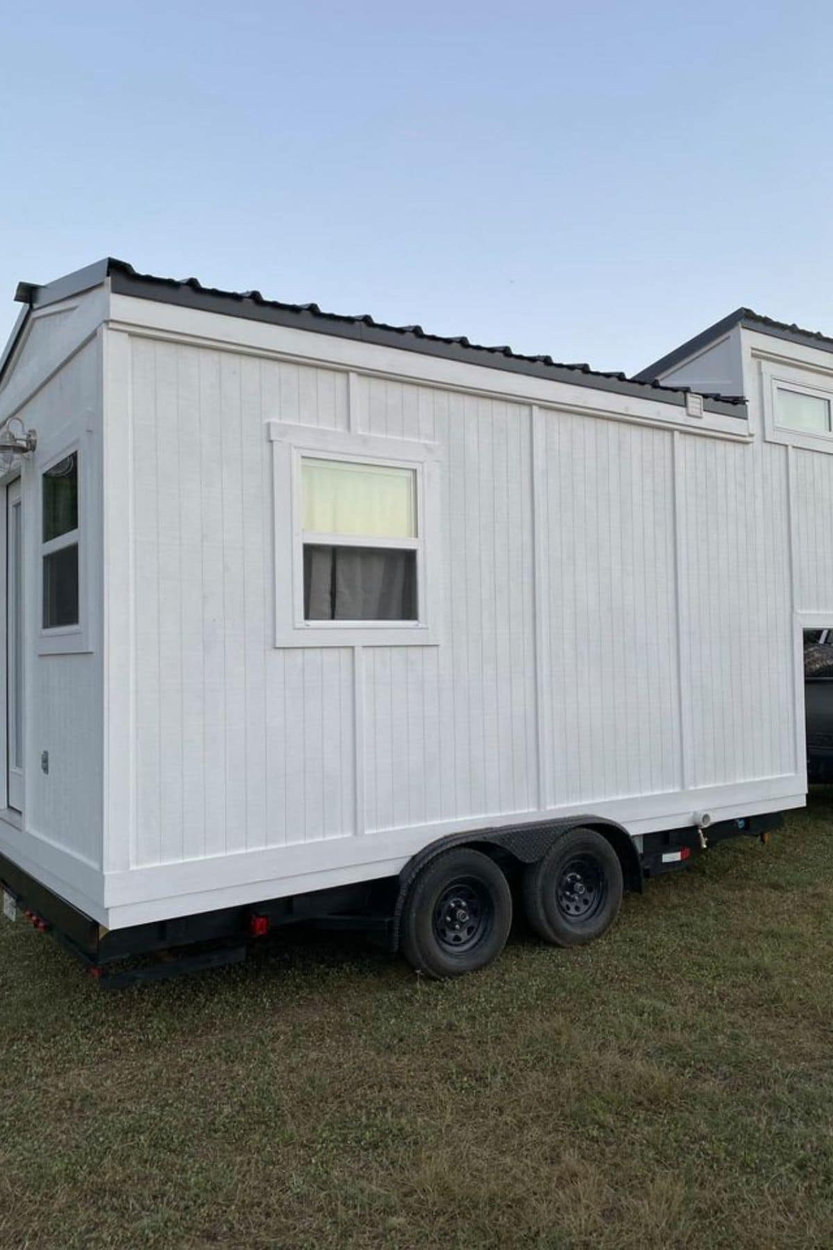 Side of white tiny house on wheels with one window on side