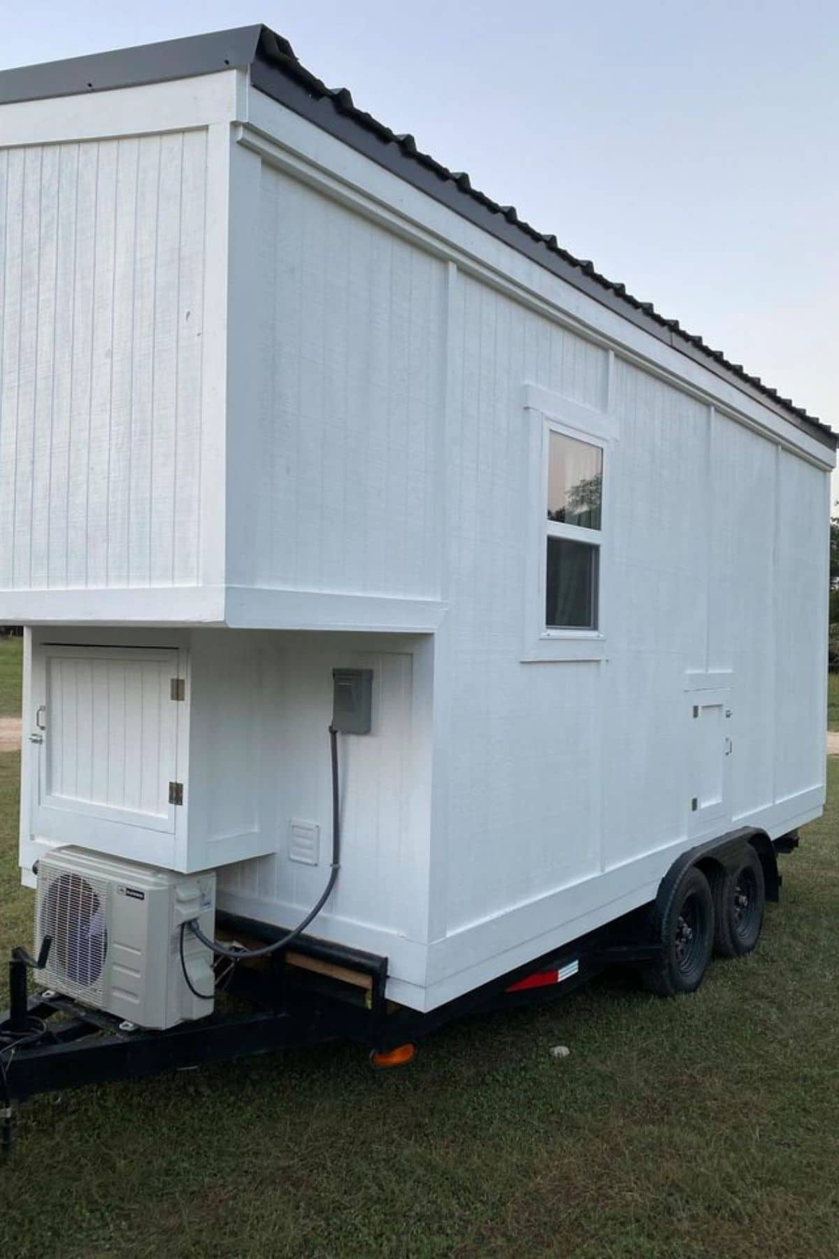 End of white tiny home showing air conditioning unit at bottom by hookups