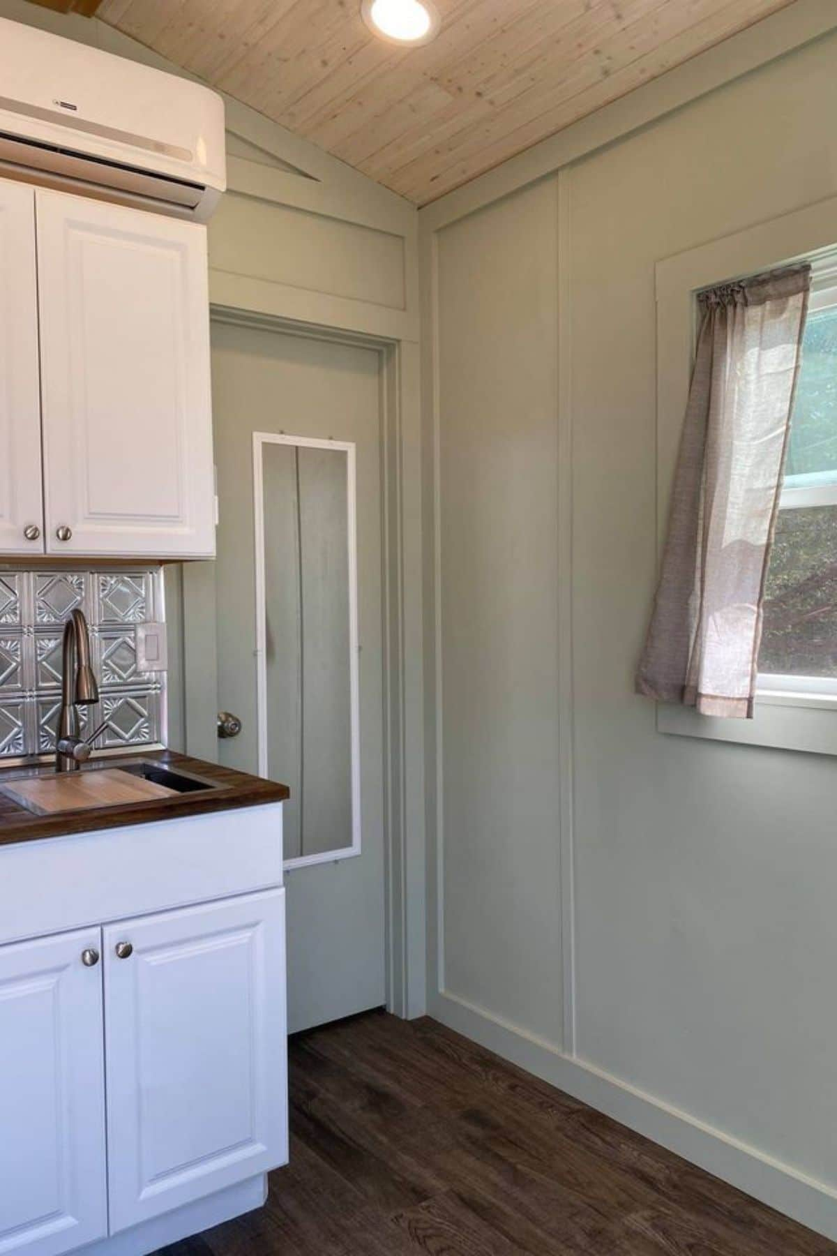 Door next to end of kitchen counter by sink