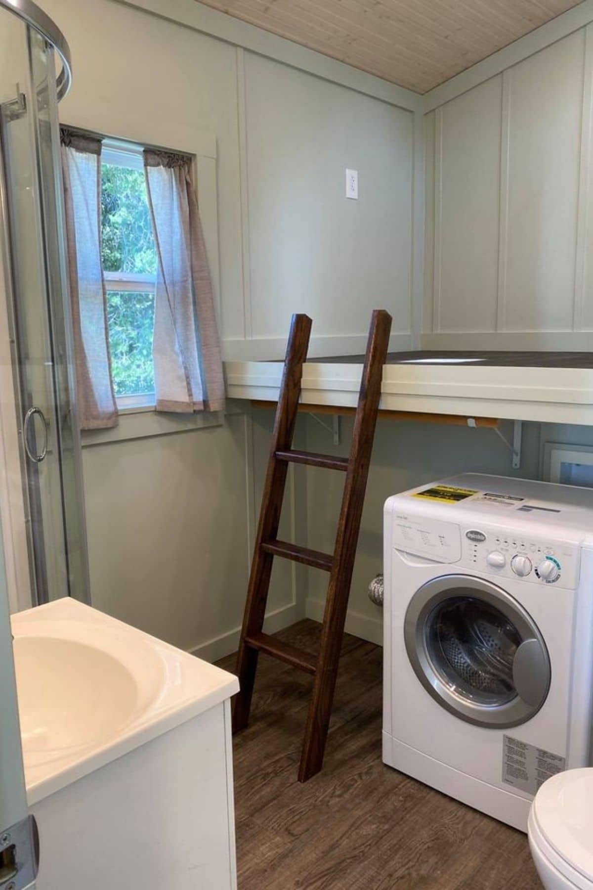 Loft space above washing machine with wood ladder