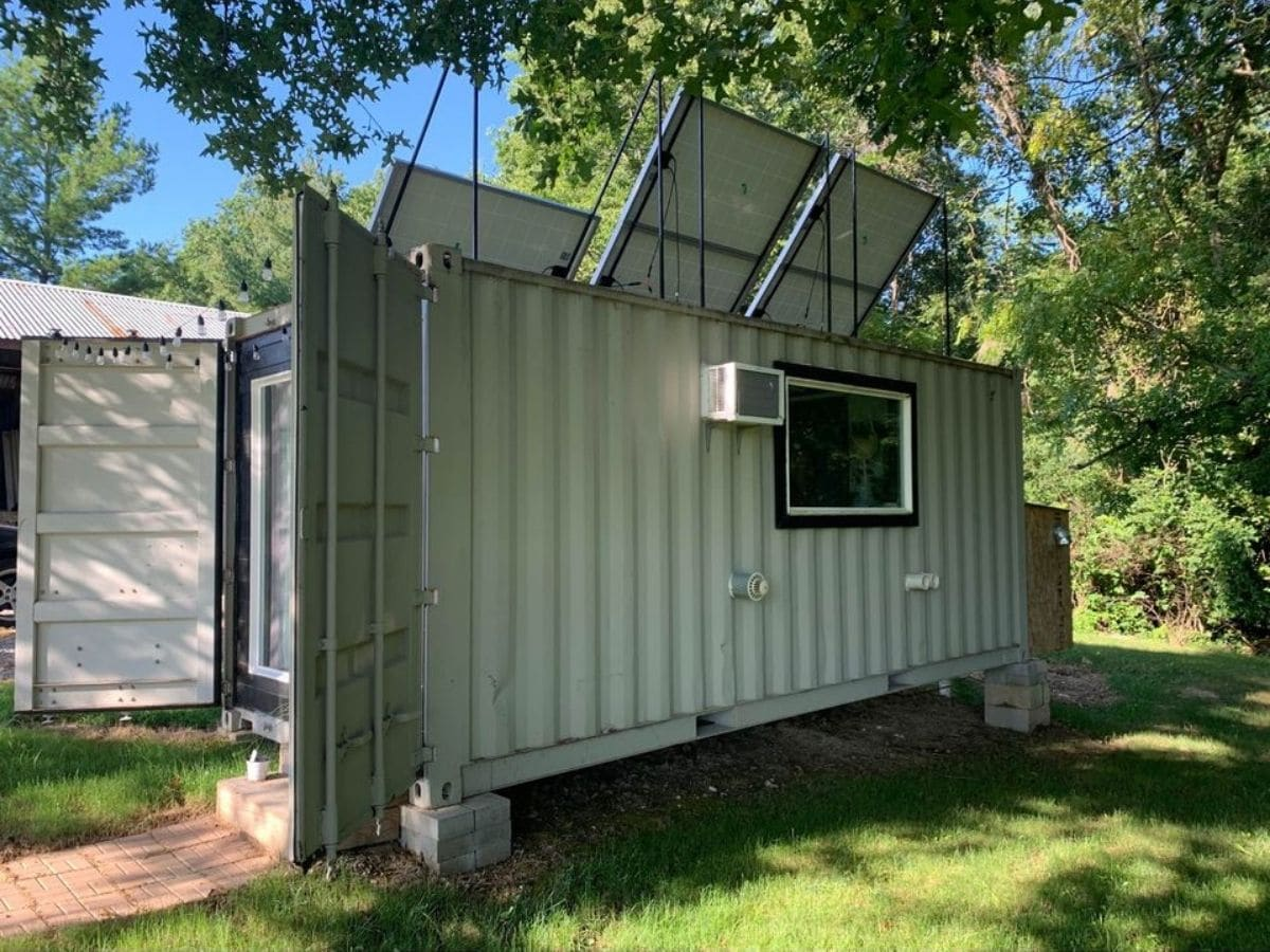 Side of container home on blocks with doors open on end