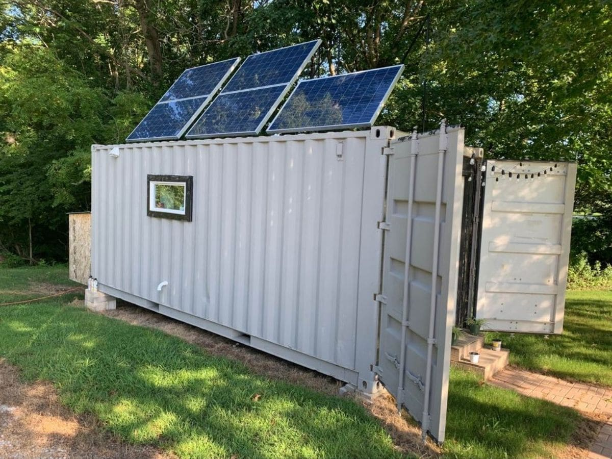 Side of tiny home with single window and solar panels on top