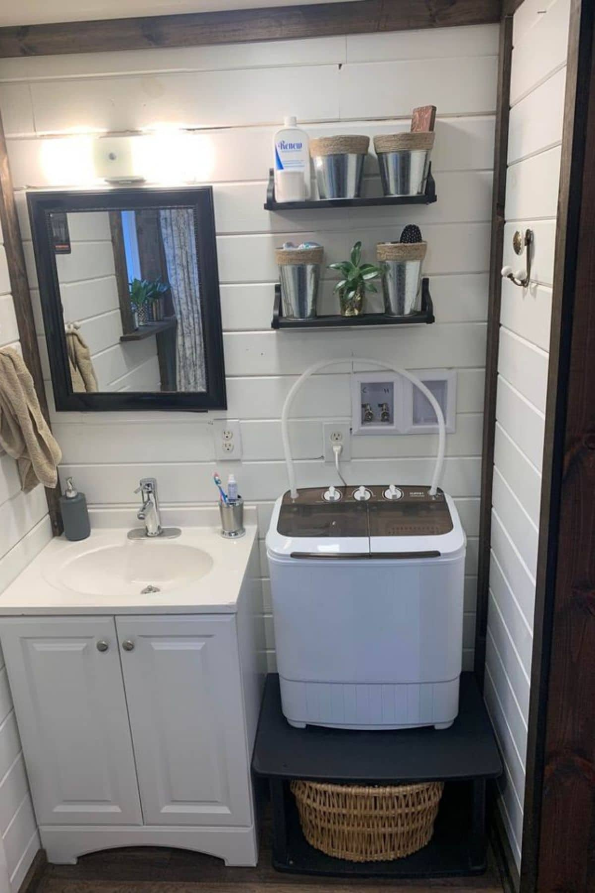 Bathroom with sink and portable washing machine on bench
