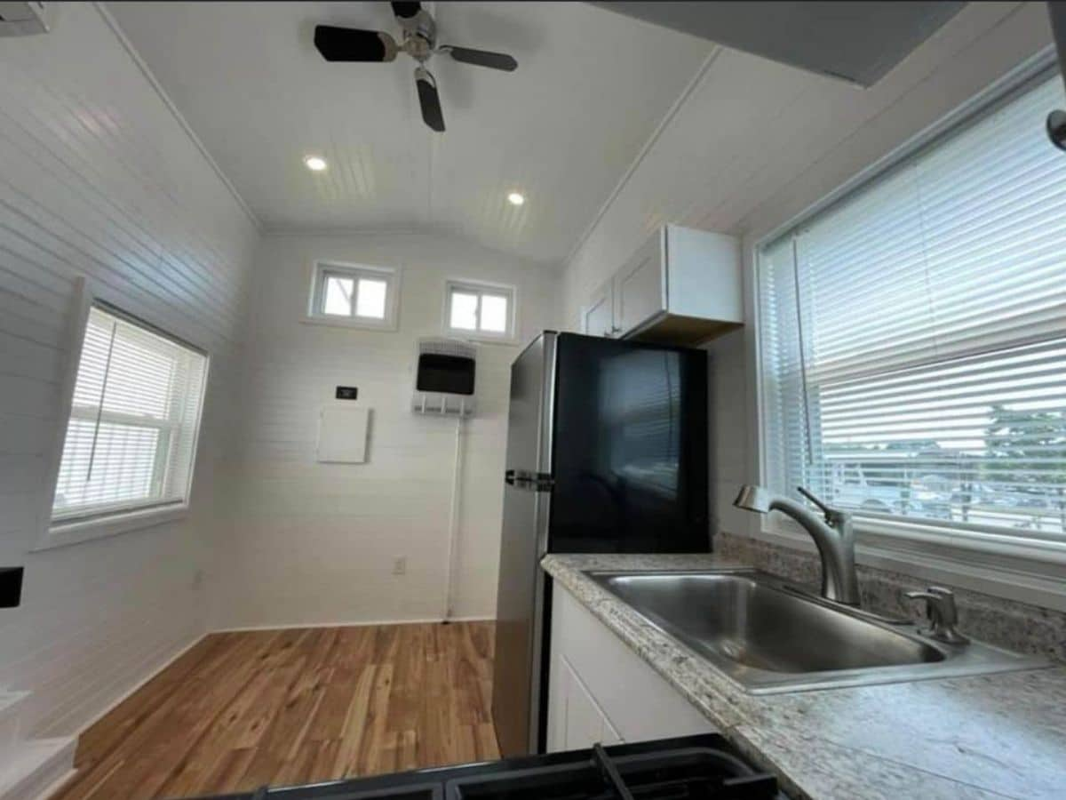 Black refrigerator at end of kitchen counter