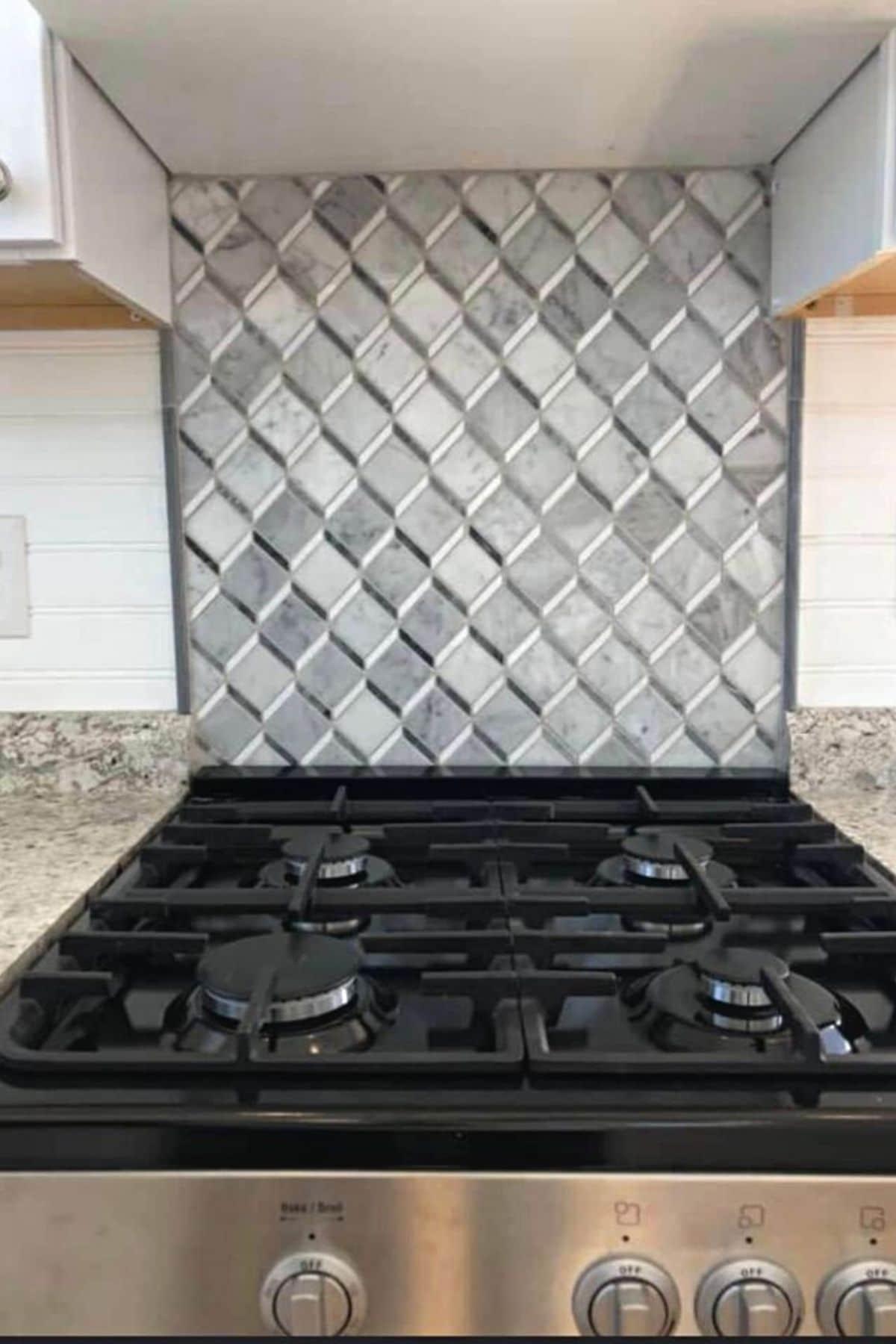 Tiled backsplash behind gas stove