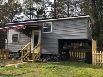 Gray tiny house with maroon awning