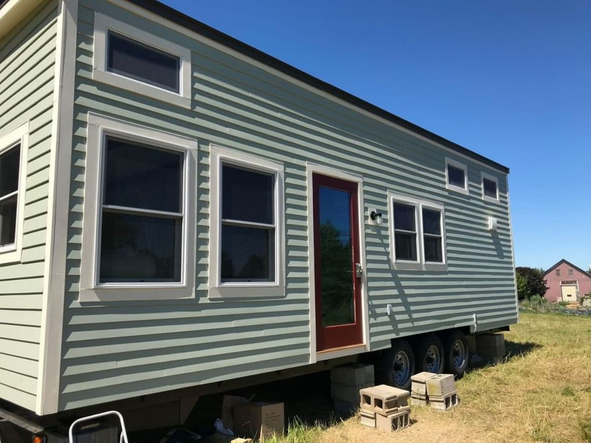 Front ofgreen tiny home with 6 windows and glass door with red trim