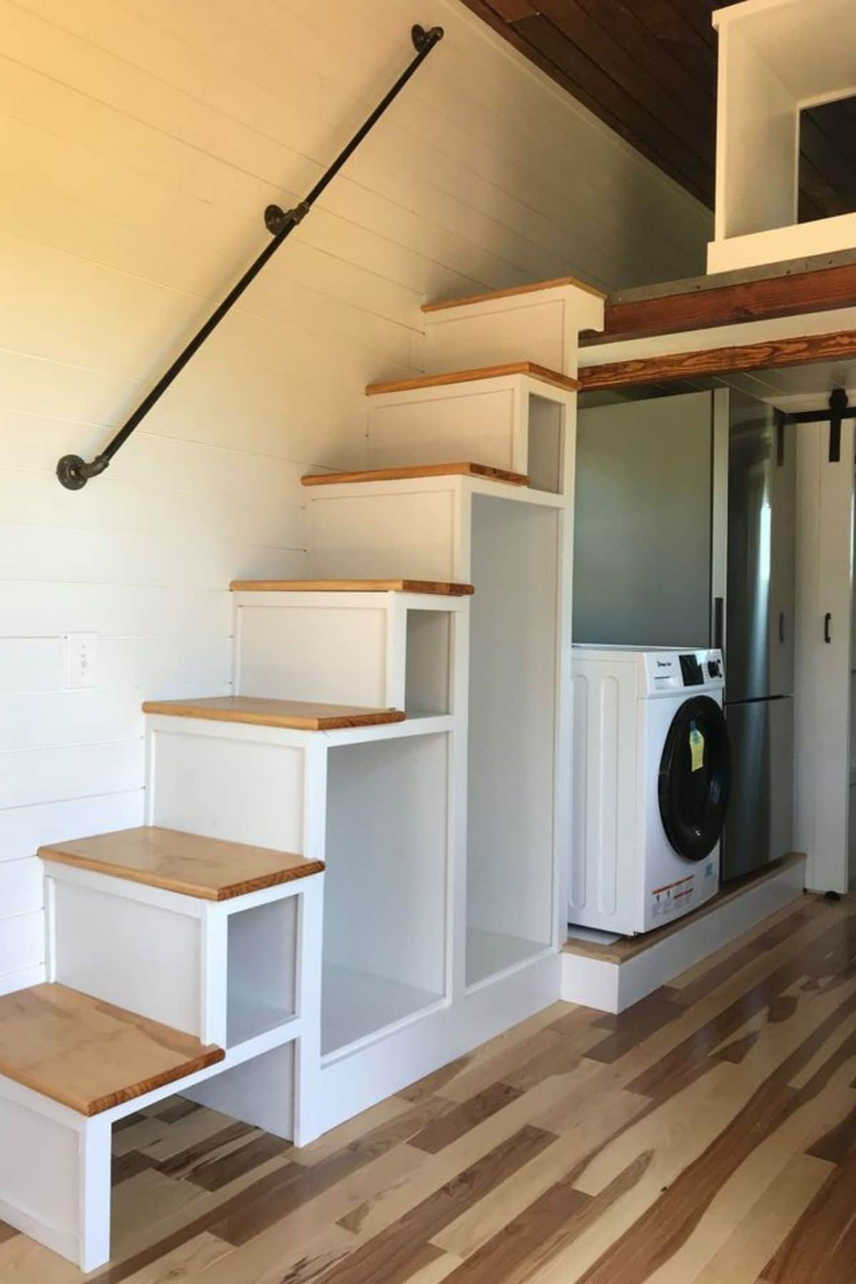 Stairs against white wall with washing machine under back of stairs