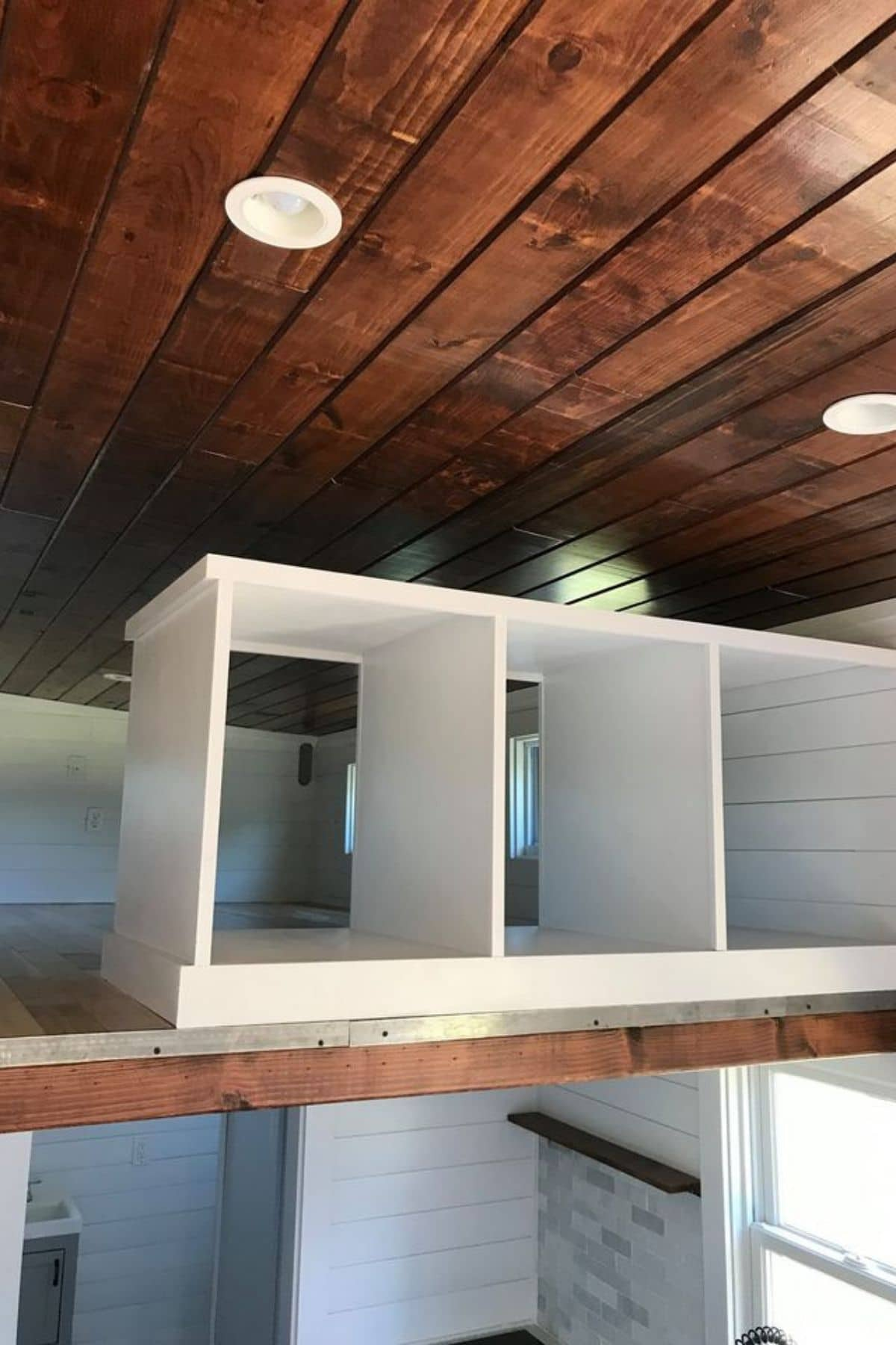 Open white cubbies in tiny home loft