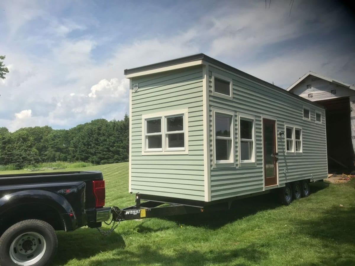 End of tiny home with green siding attached to back of black truck