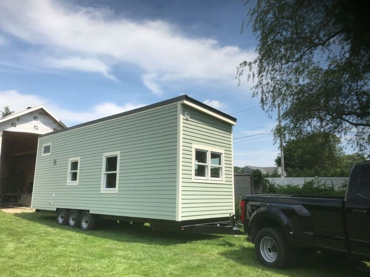 Back side of green tiny home pulled by black ruck