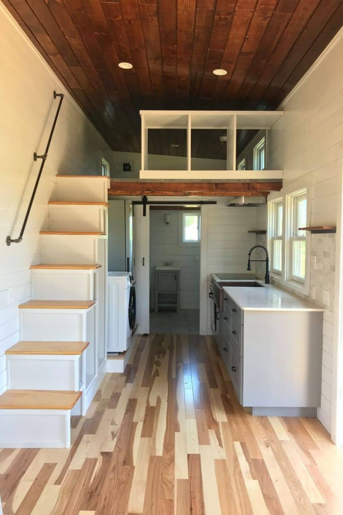 Tiny home living space with stairs on left and kitchen on right