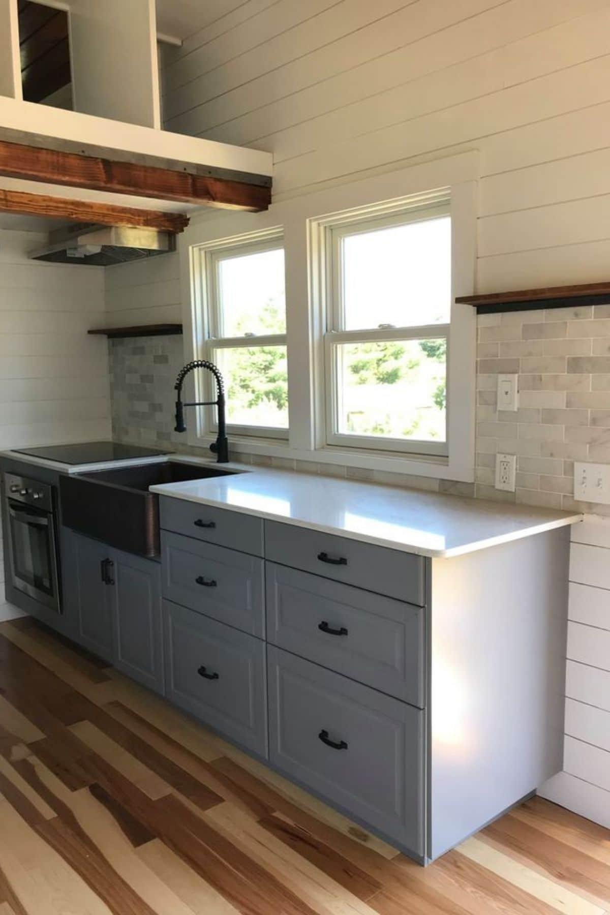 Gray kitchen cabinets with tile backsplash