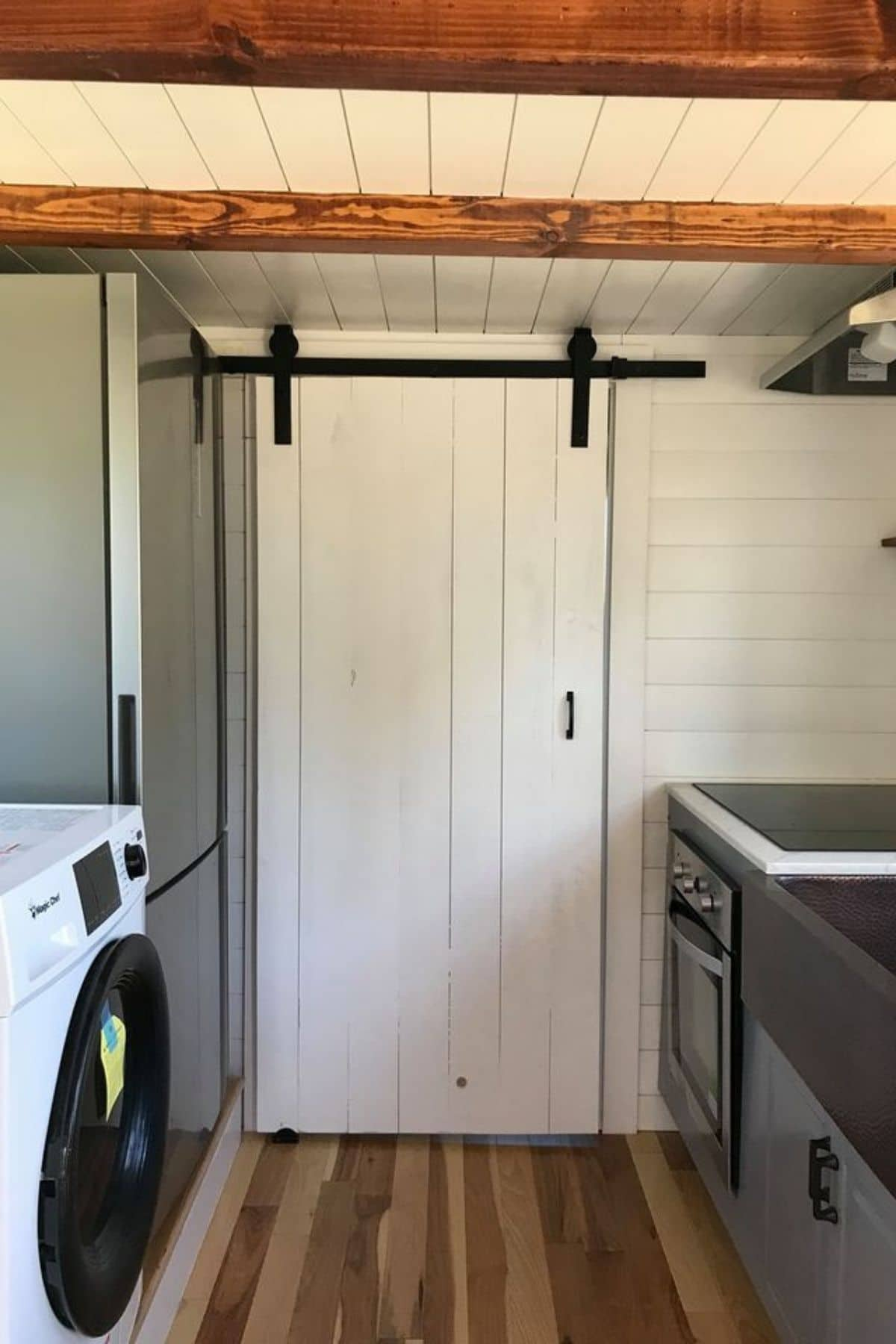 White barnhouse door against back of kitchen wall