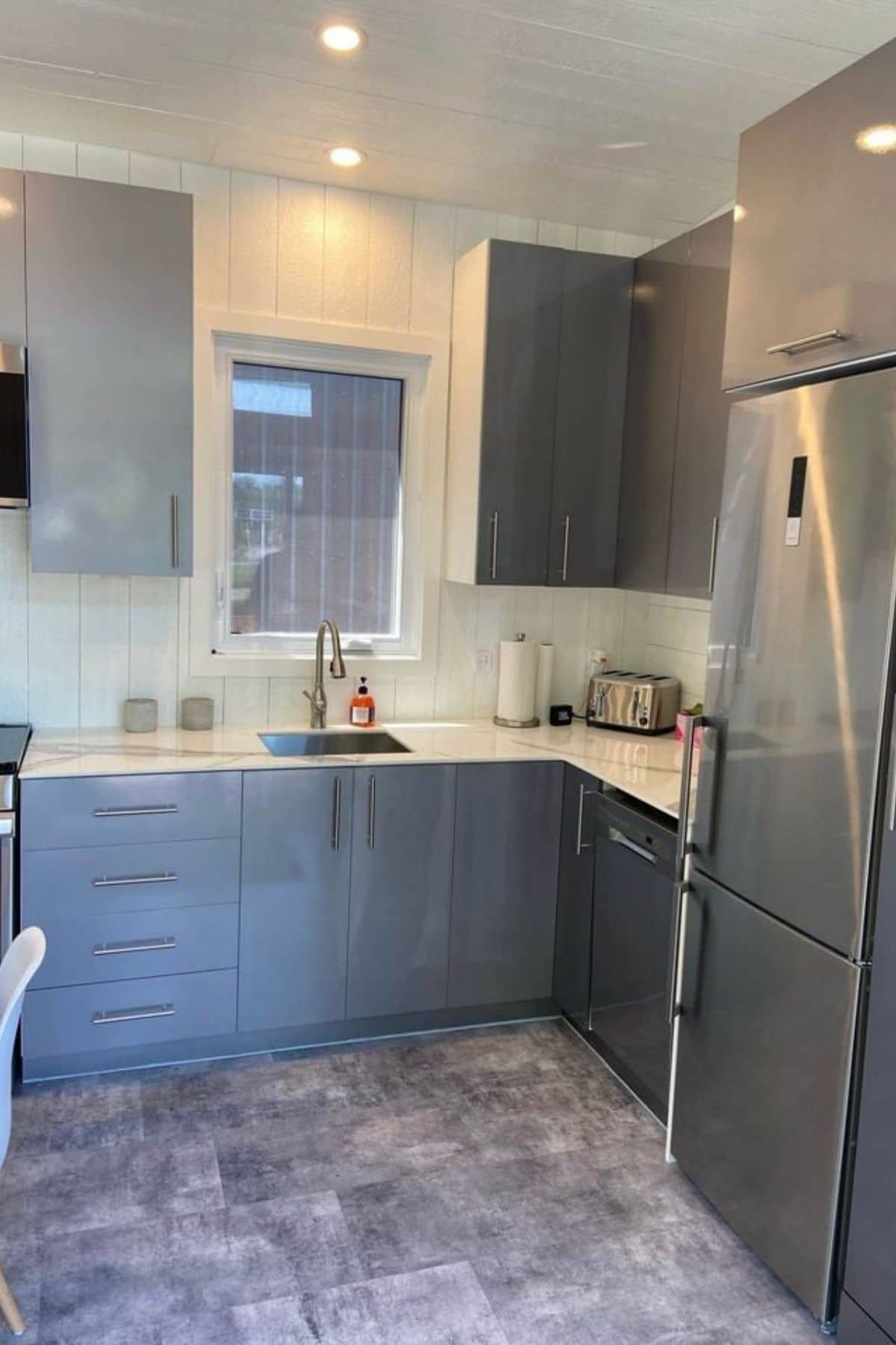 Gray cabinets and stainless steel refrigerator intiny kitchen