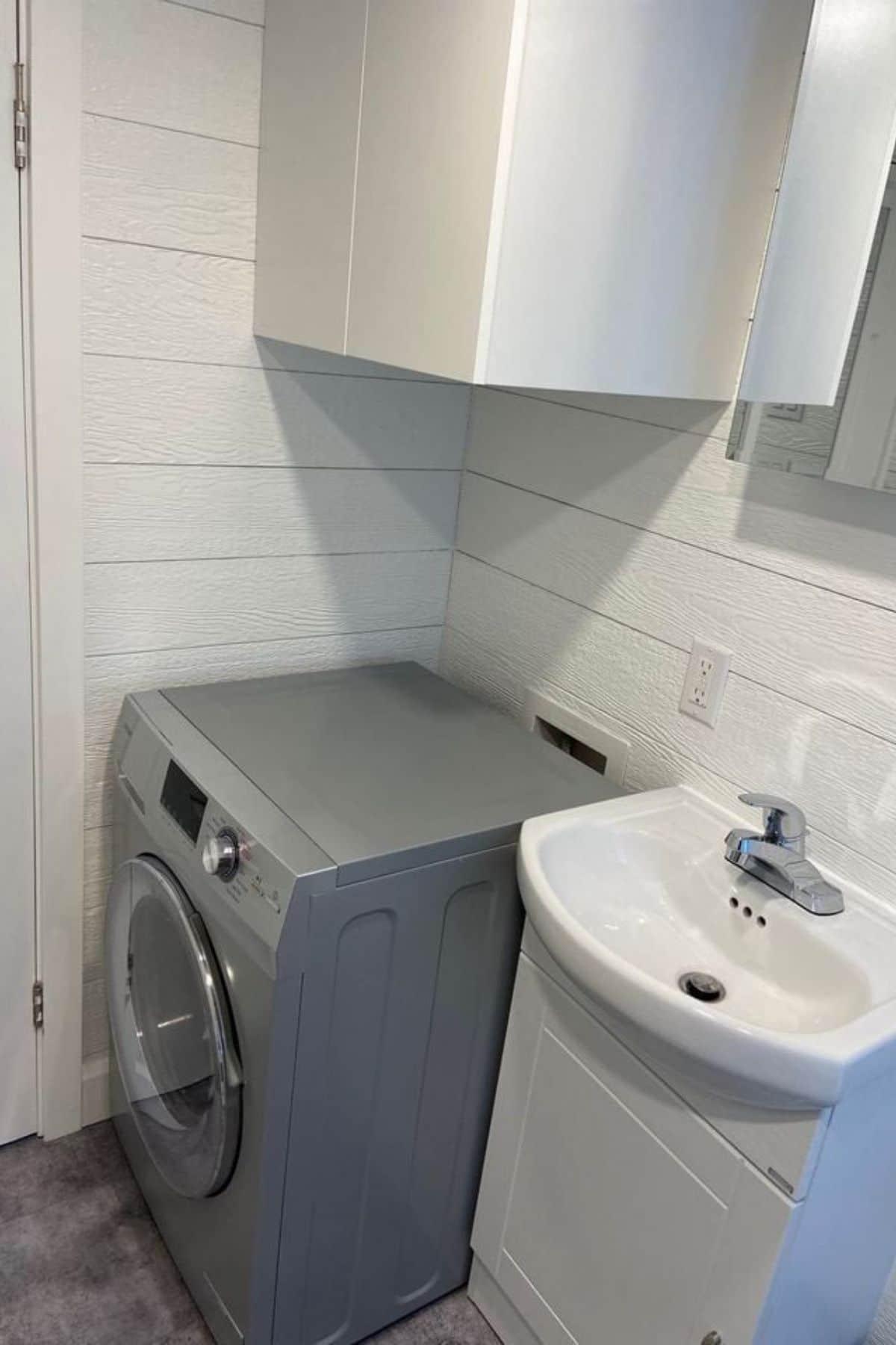 Gray washing machine next to white sink