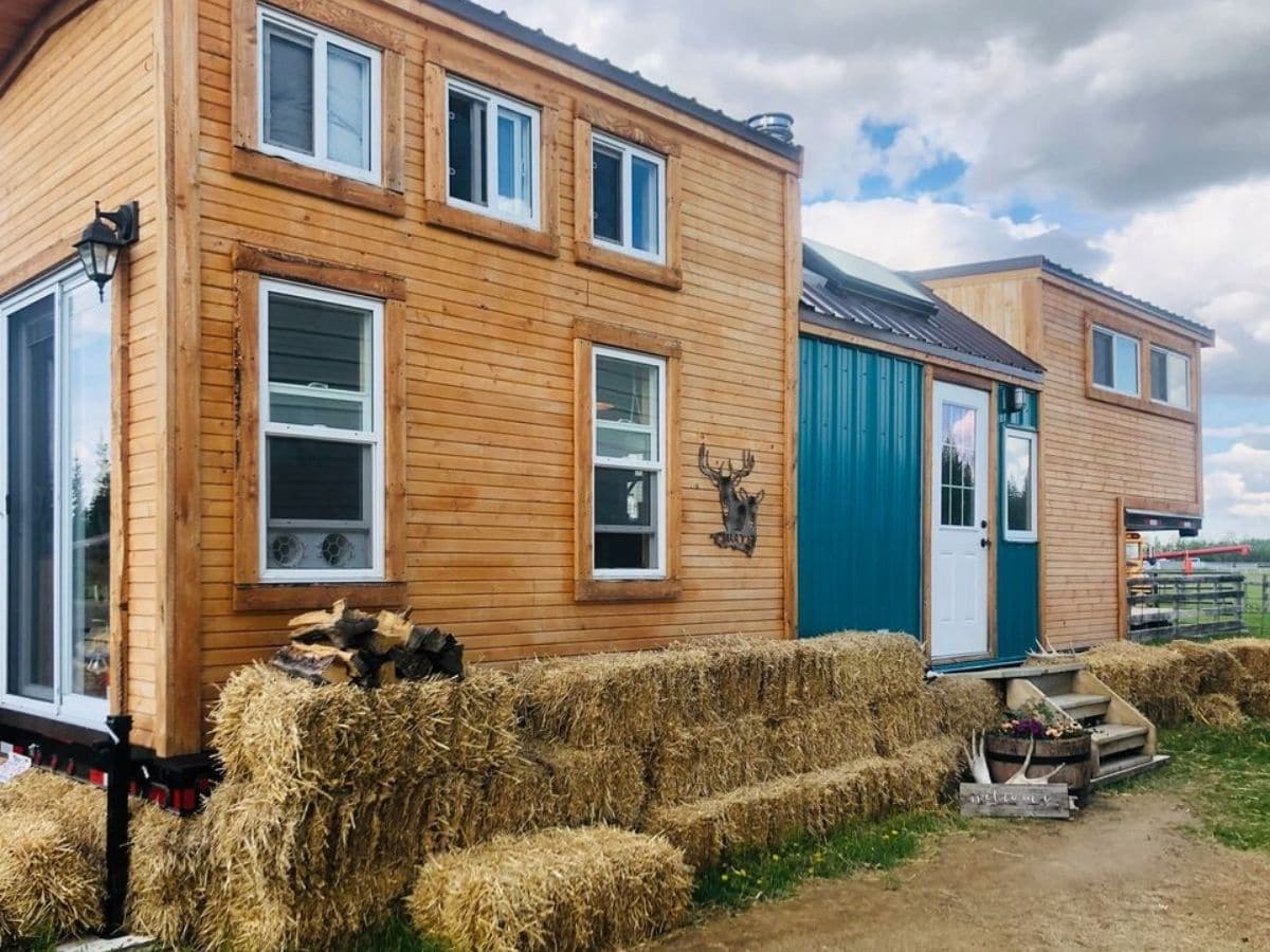 Side of wood tiny home with teal accents