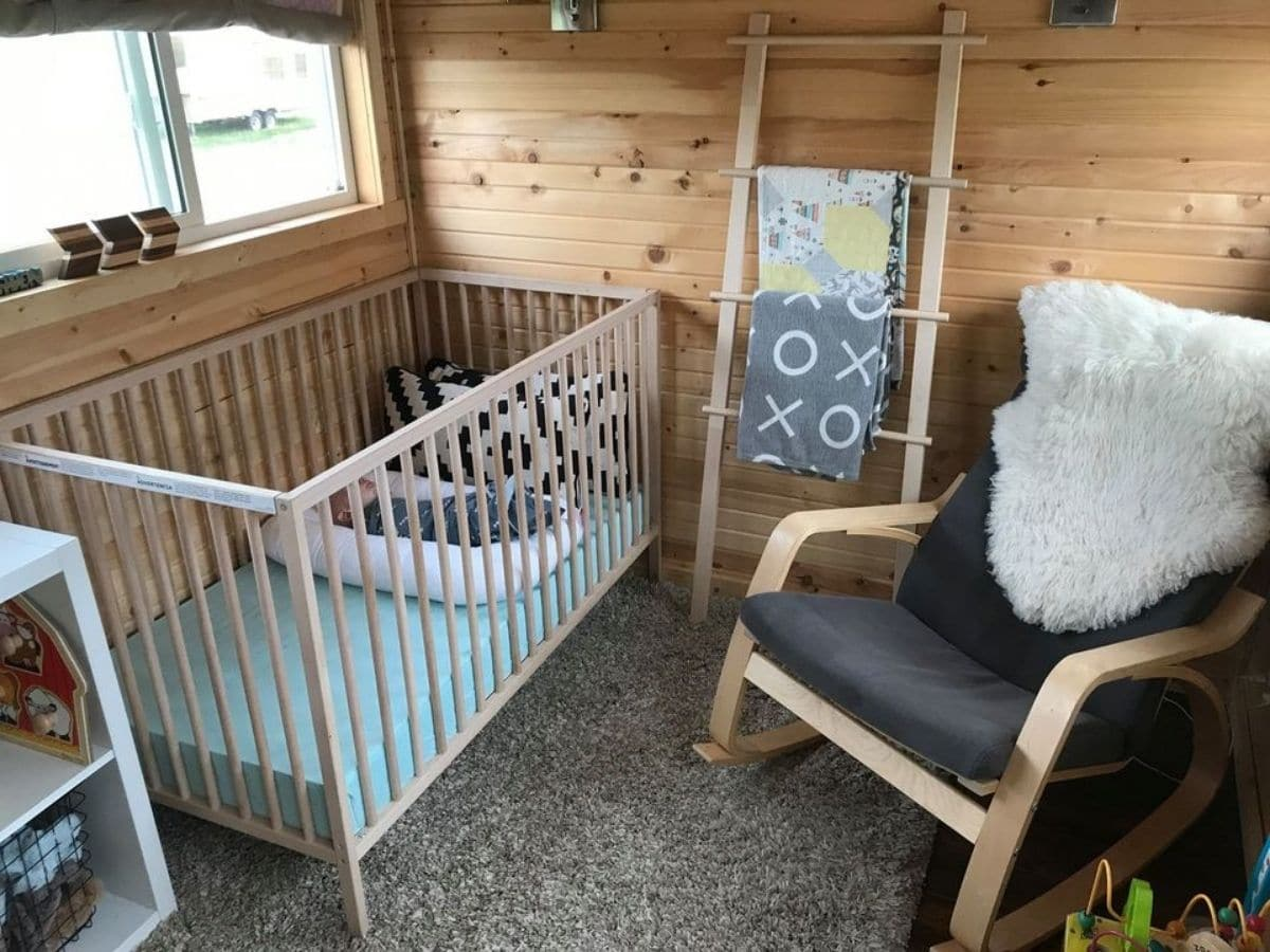 Crib against wall in wooden room