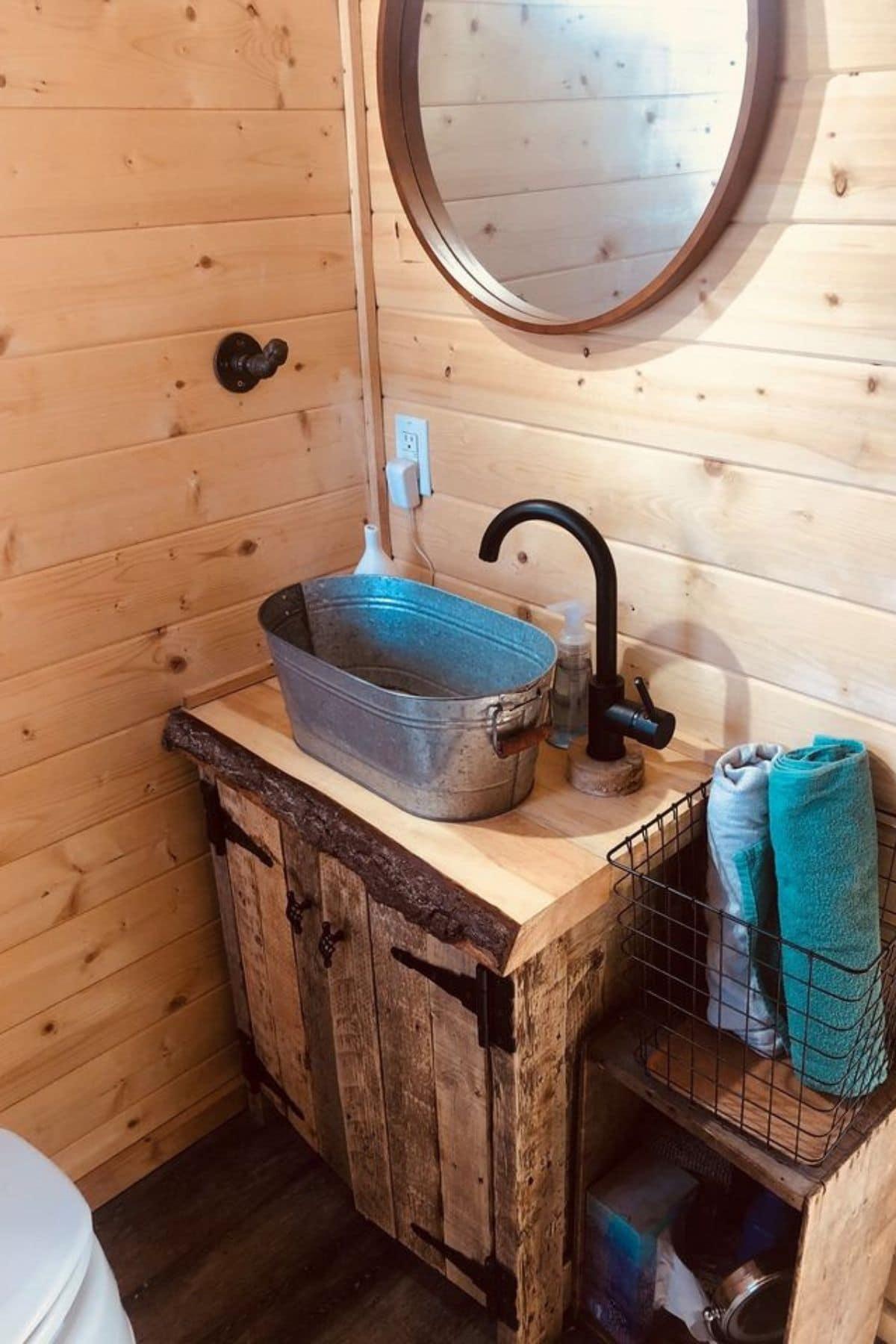 Galvenized bucket sink in tiny wood bathroom