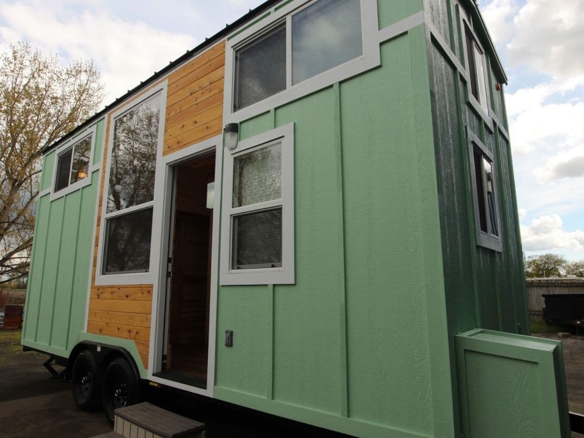 Green tiny home with wood accents and white trim