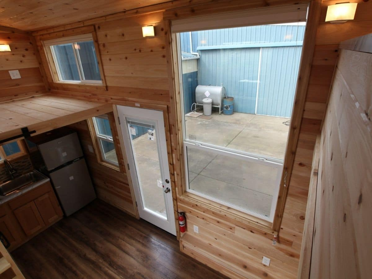Entry door with large window next to it inside wood tiny home