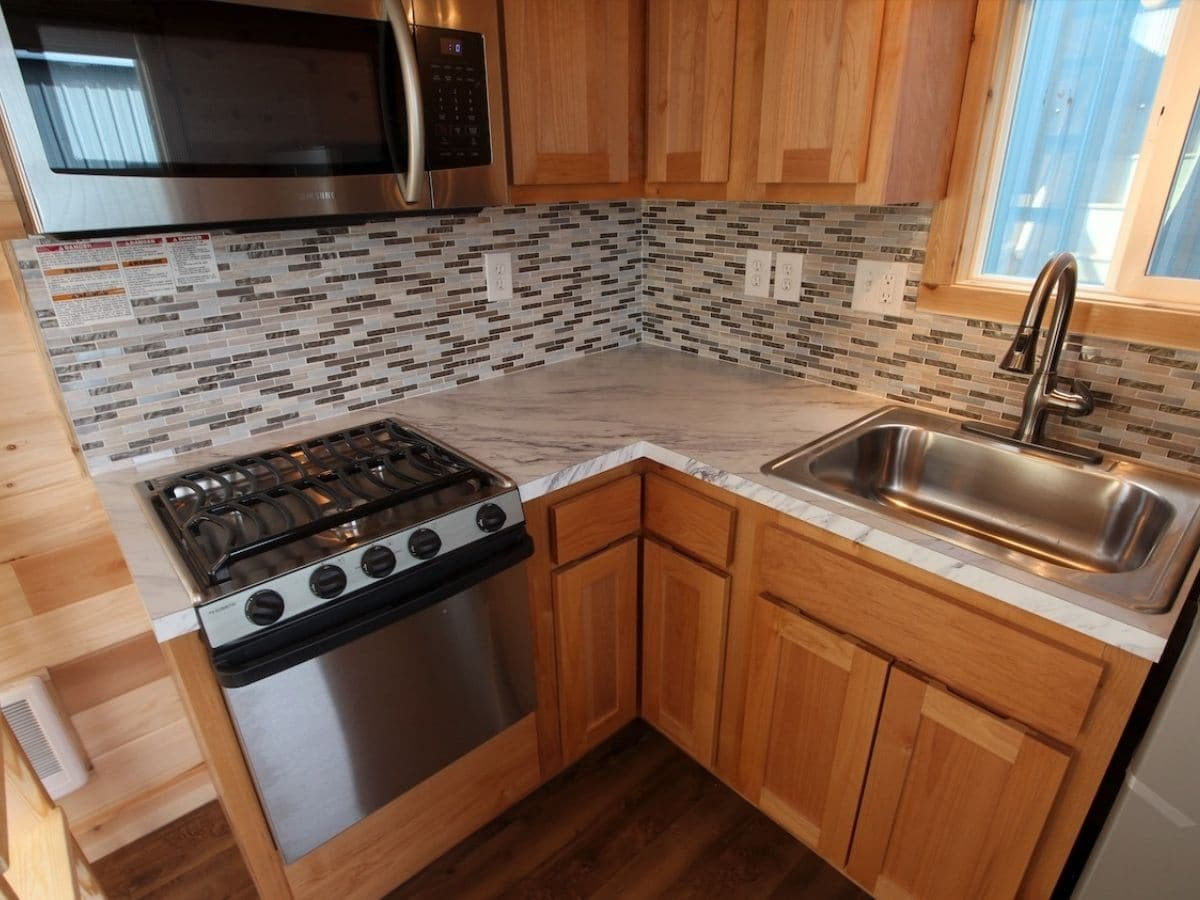 Corner kitchen with tiled back splash and rv stove