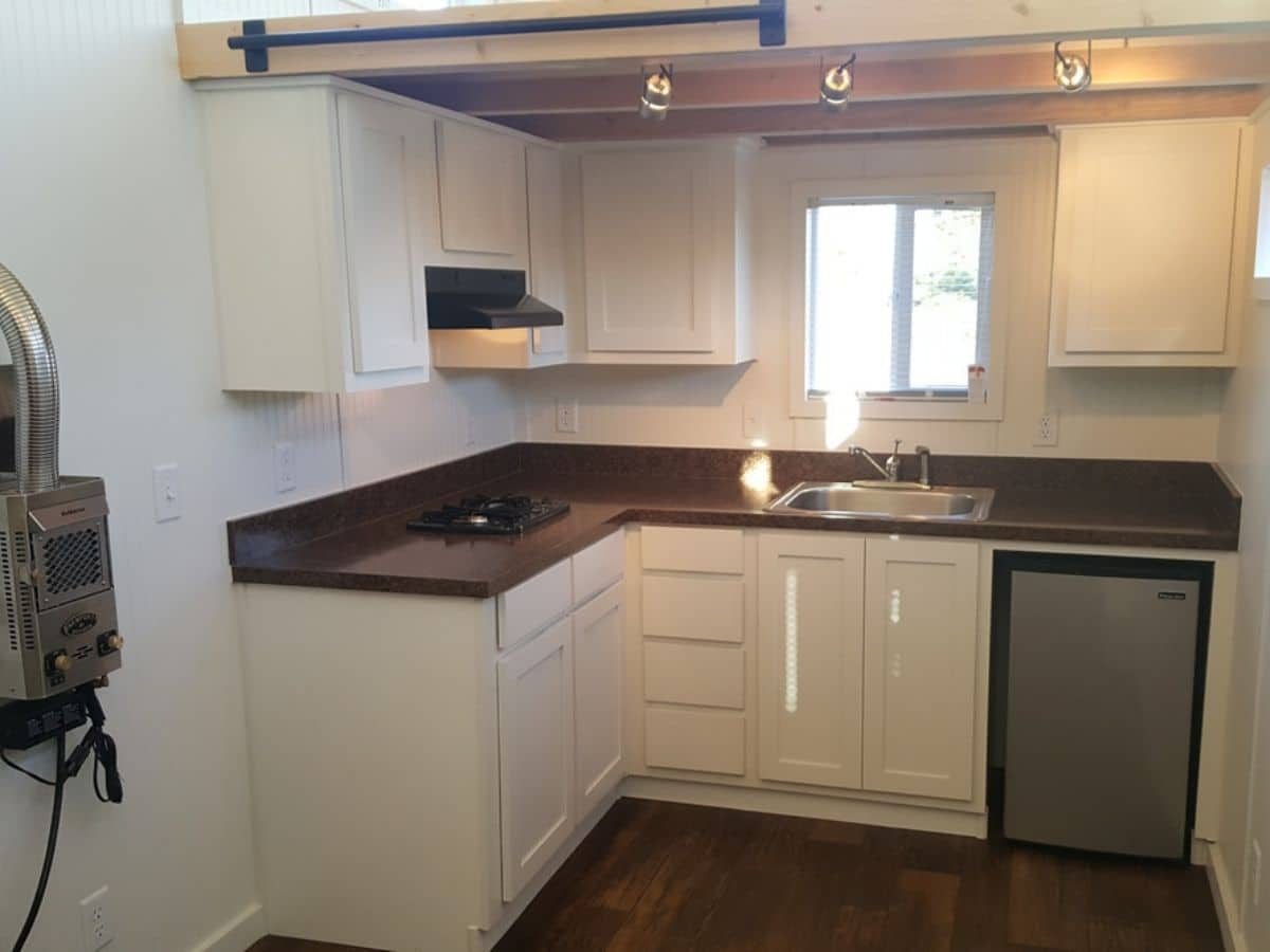 White cabinets and walls in kitchen with dark wood counter