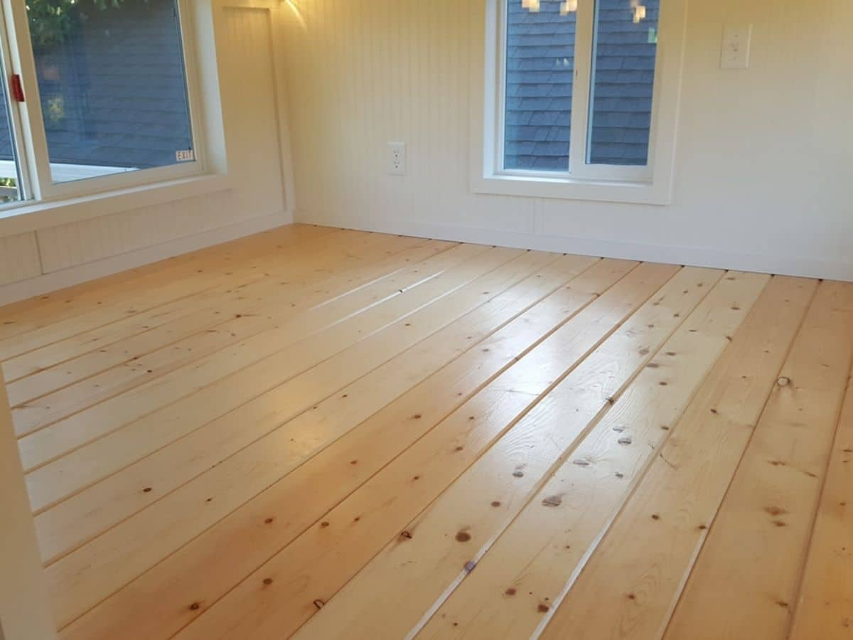 Light wood floors with white walls and large windows in tiny home loft