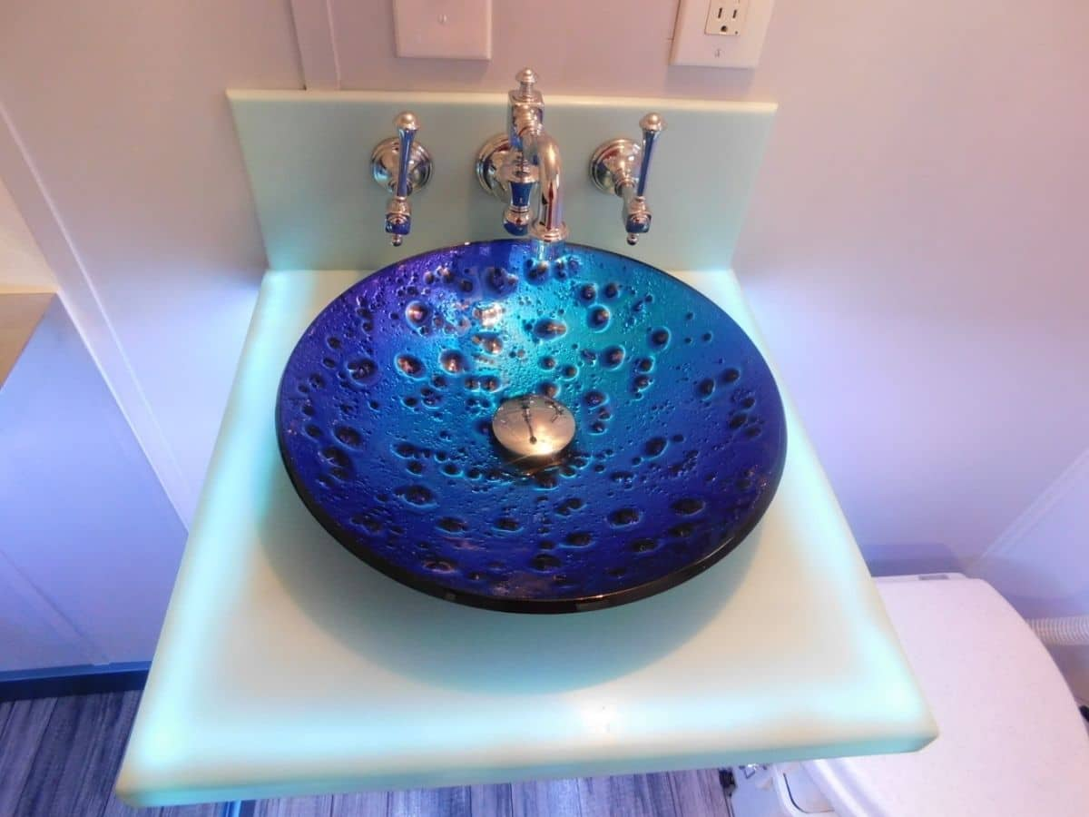 Light teal base with dark blue bowl sink agaisnt wall