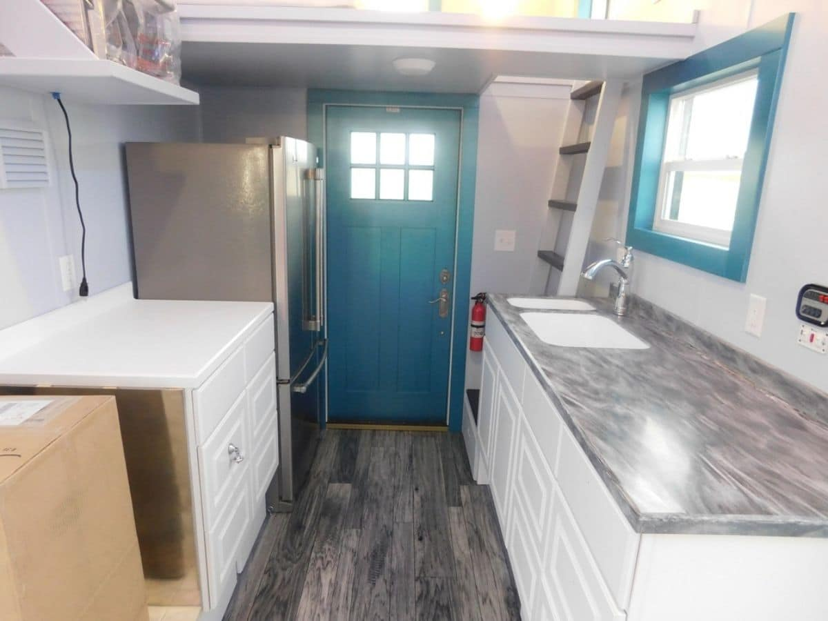 Kitchen counter on right with large refrigerator on left